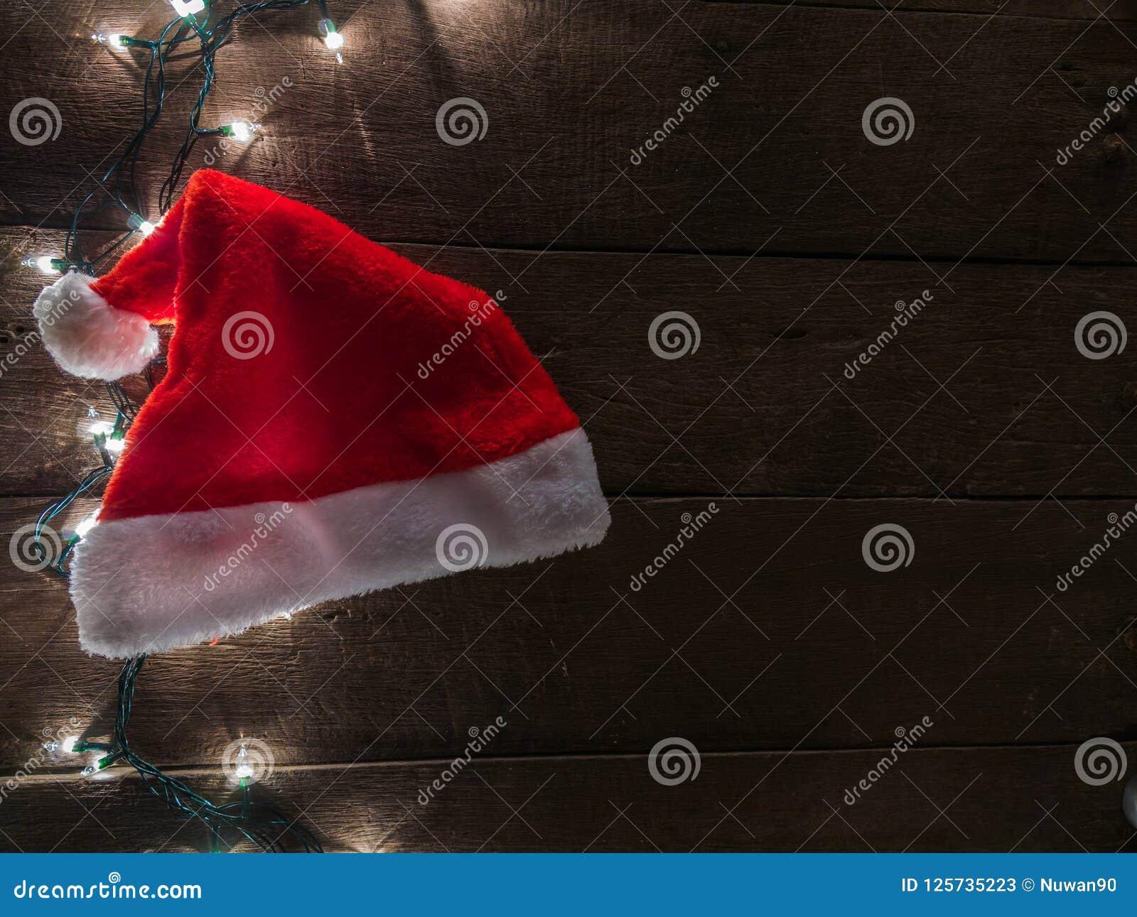 Ljus för jultomten hatt och julpå träskrivbordbakgrund och tömmer utrymme för text Bästa sikt med kopieringsutrymme