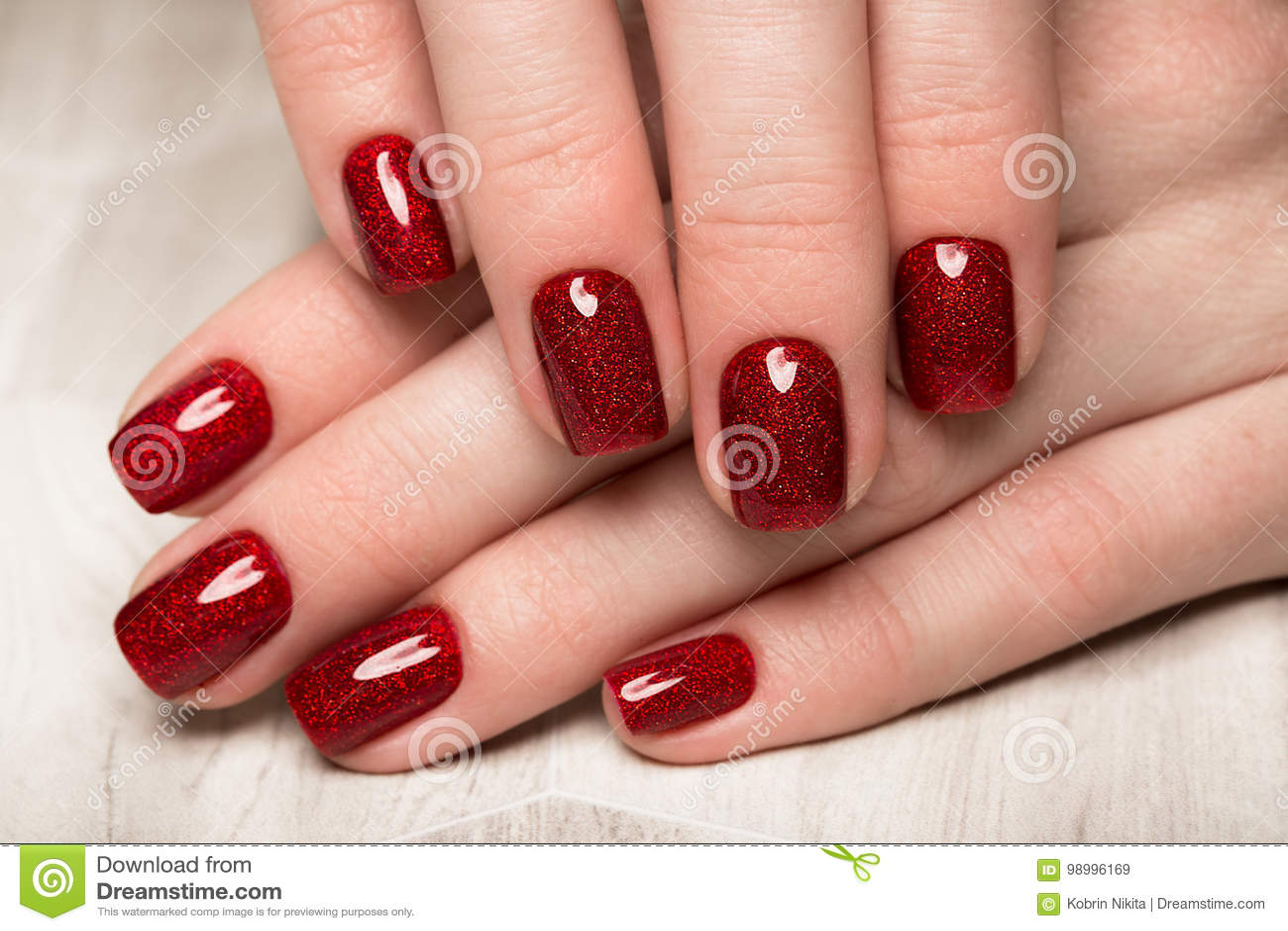 Ljus festlig röd manikyr på kvinnliga händer Spikar design