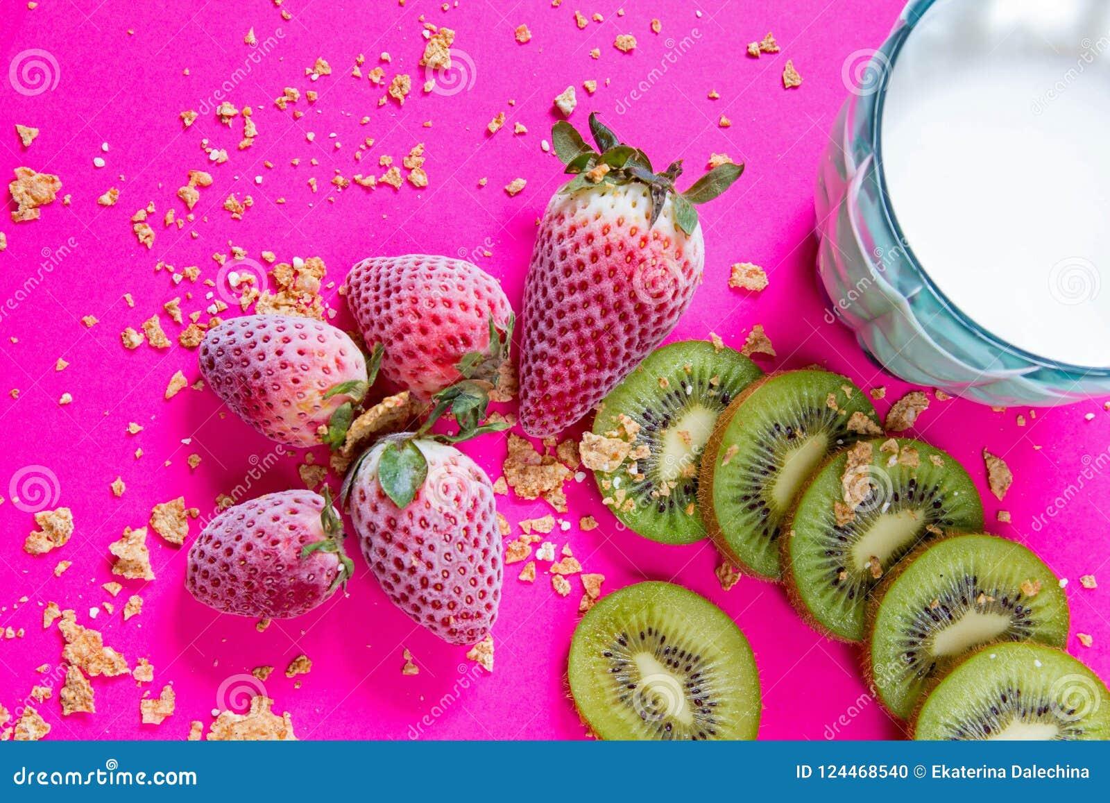 Ljus frukostbild - sädesslag, blått exponeringsglas av kon mjölkar och frukter på fuchsiatabellen