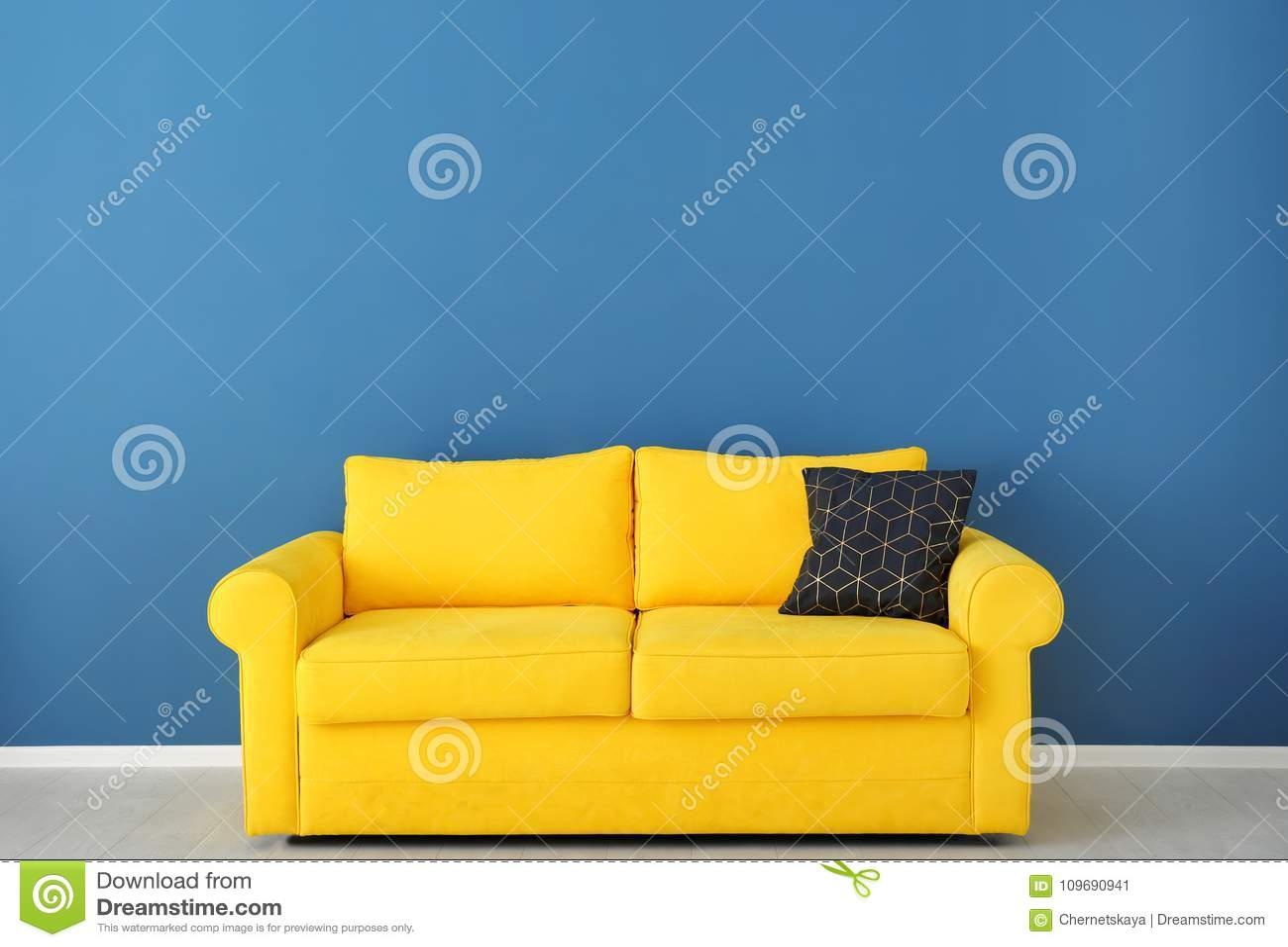 Ljus gul soffa nära väggen