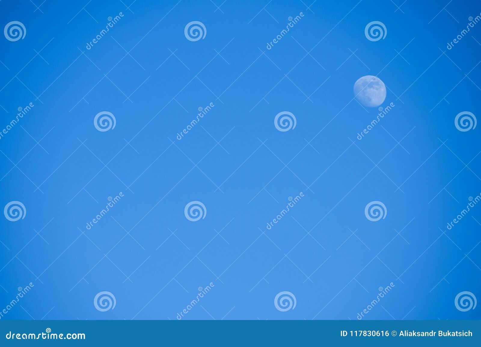 Ljus liten full blå måne mot en blå himmel i eftermiddagen, bakgrund, copyspace