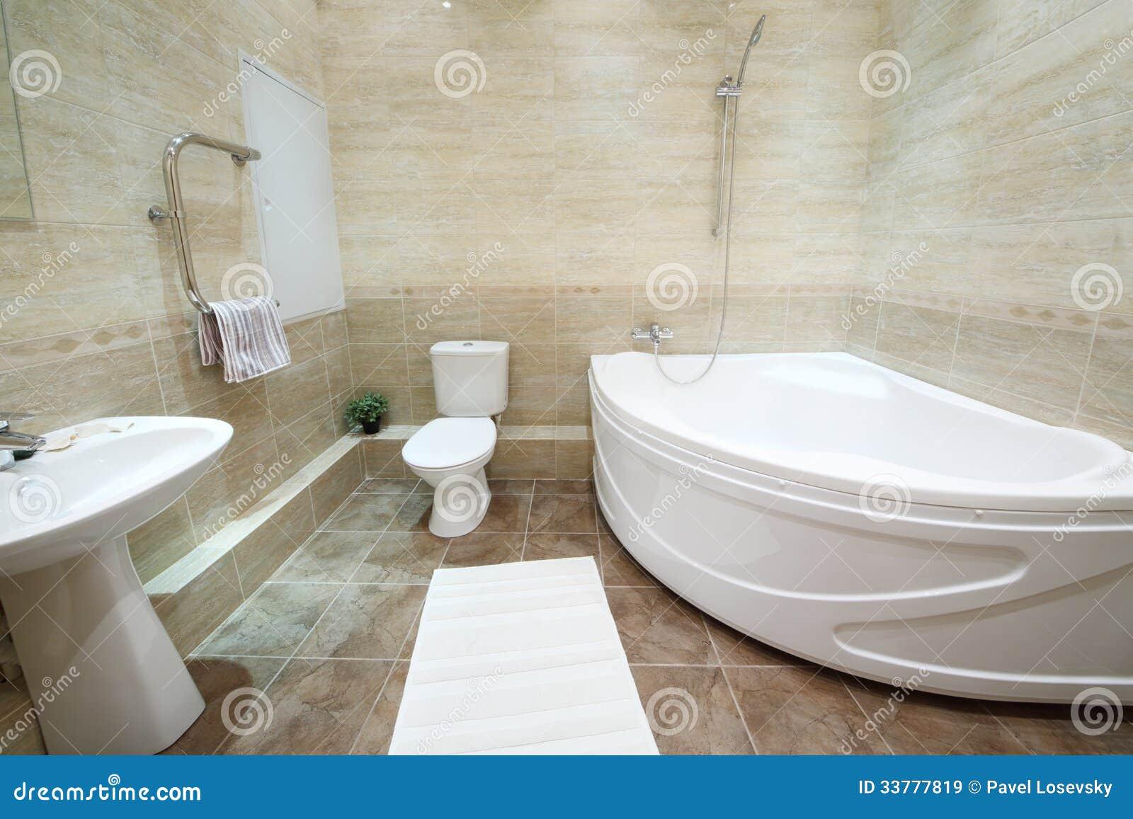 Ljus och rent badrum med toaletten med tegelplattor på golv ...