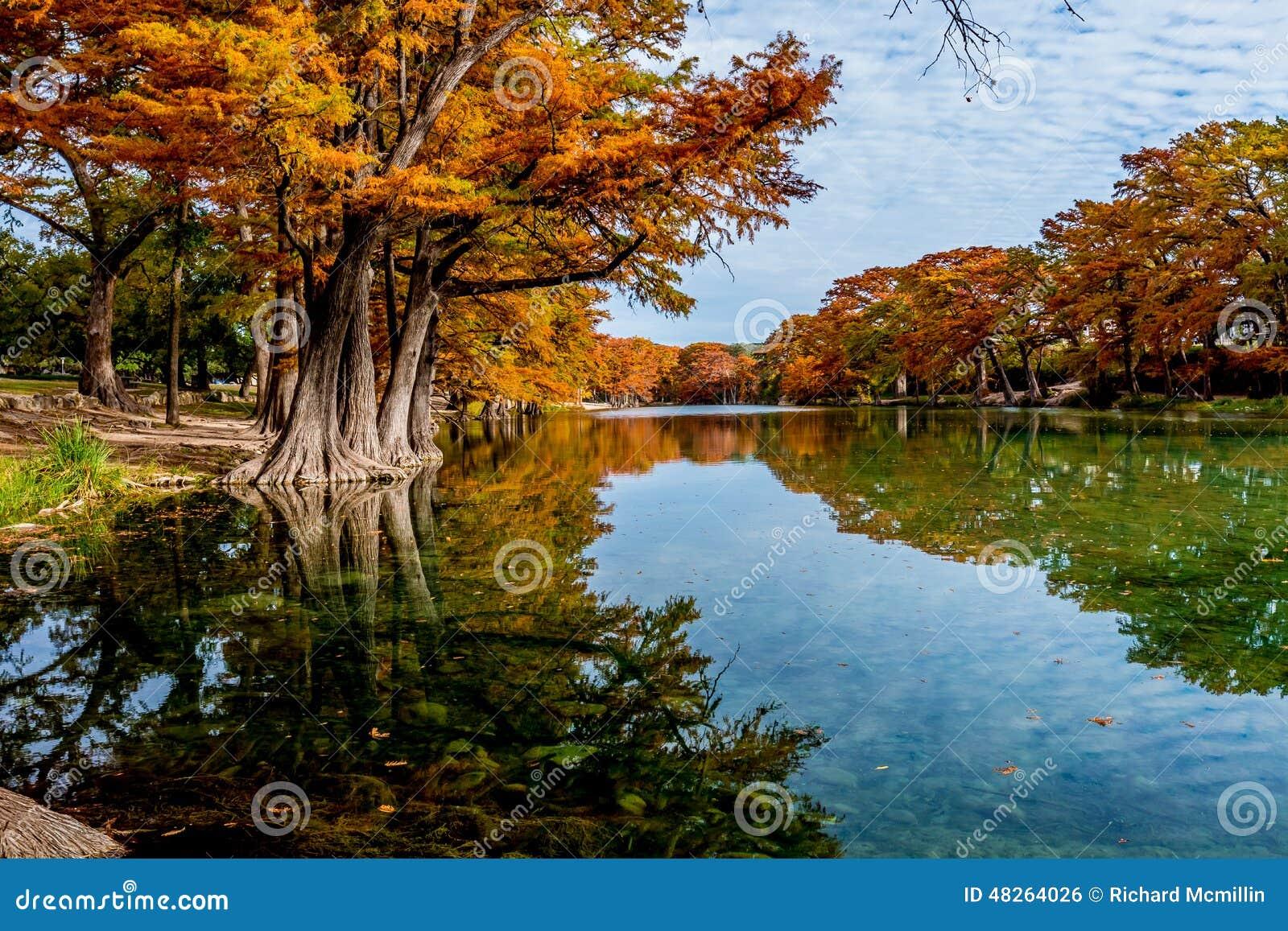 Ljus orange nedgånglövverk på Crystal Clear River på Garner State Park, Texas