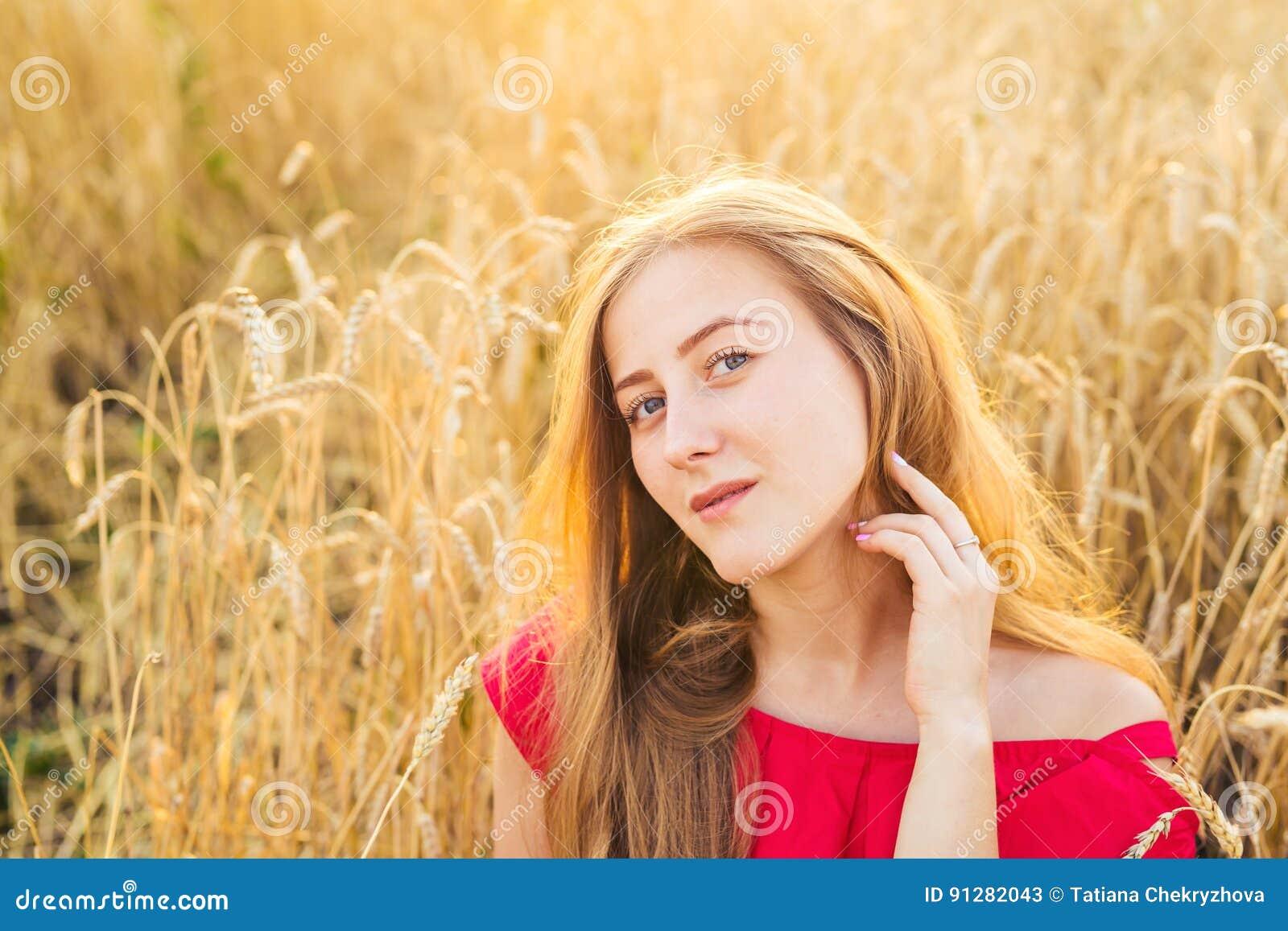 Ljus stående av den lyckliga unga kvinnan på sommarfältet