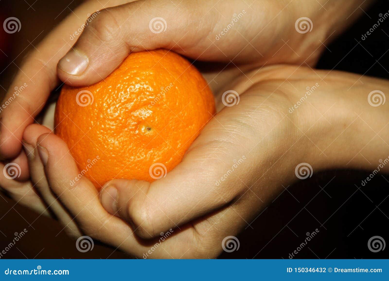 Ljus tangerin i barns händer