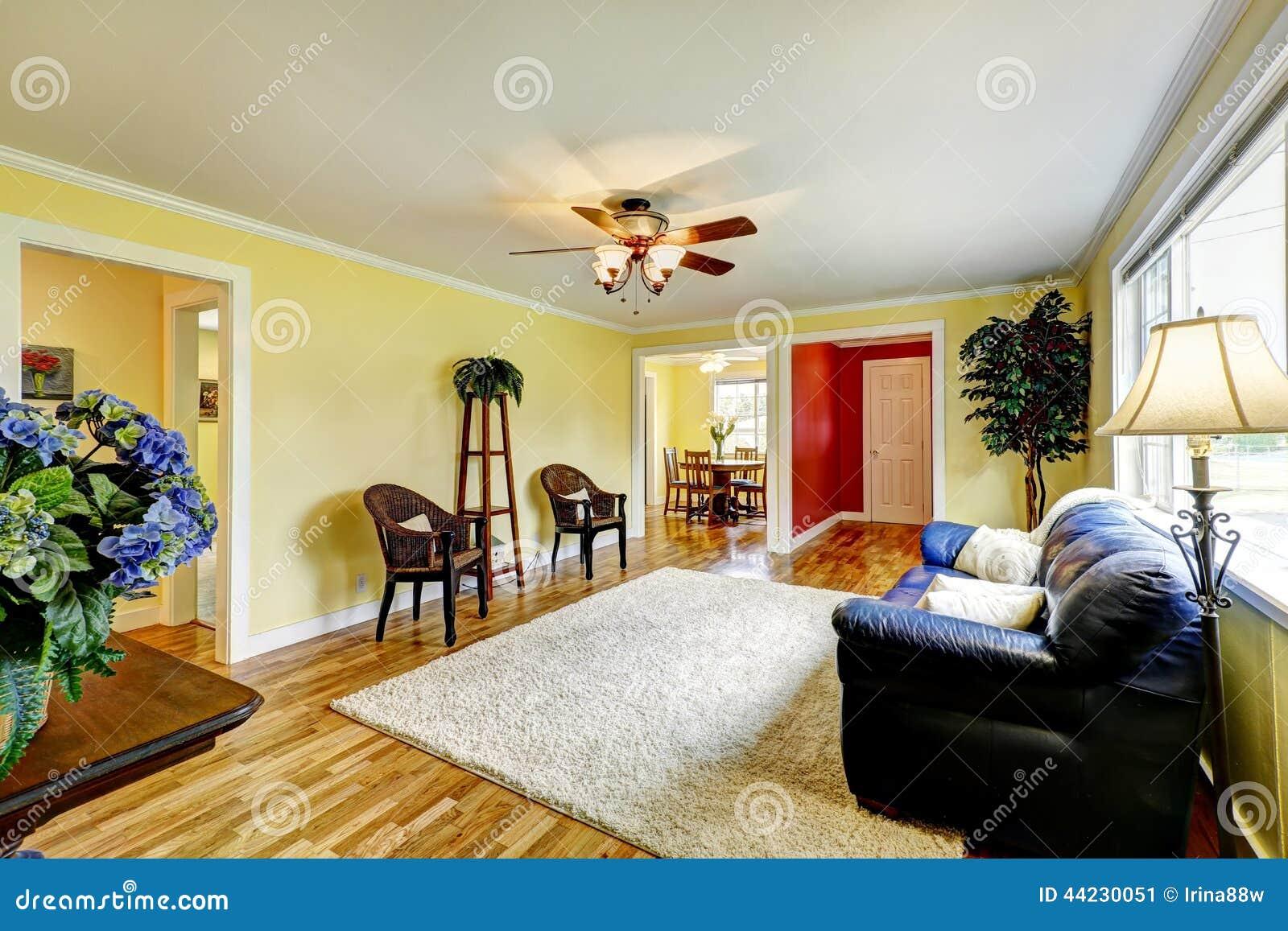 Ljus vardagsrum med gula och röda väggar arkivfoto   bild: 44230096