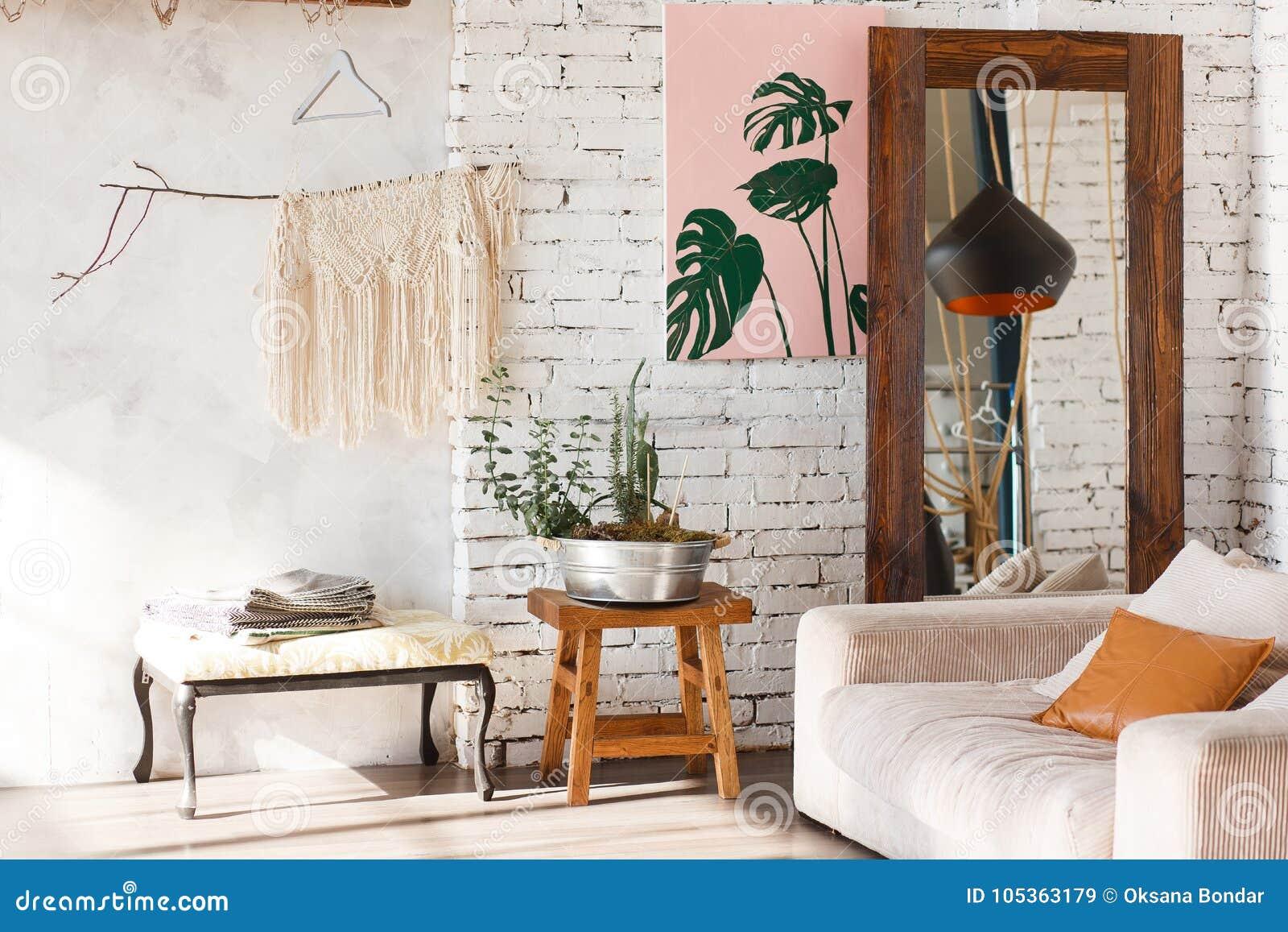Ljus vindinre med vita tegelstenväggar, spegel, modernt ljus, soffa, dekor