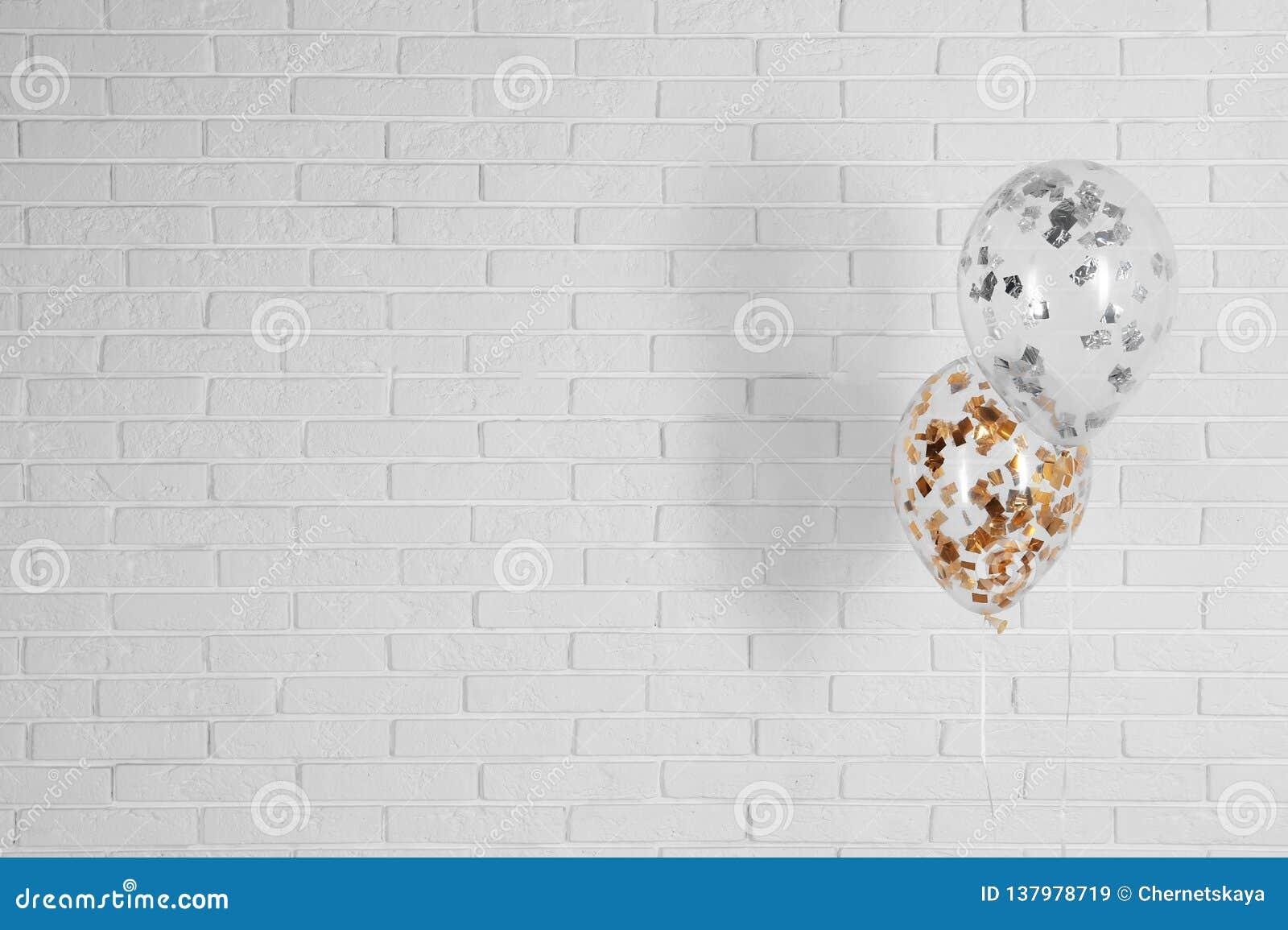 Ljusa ballonger nära tegelstenväggen, utrymme för text