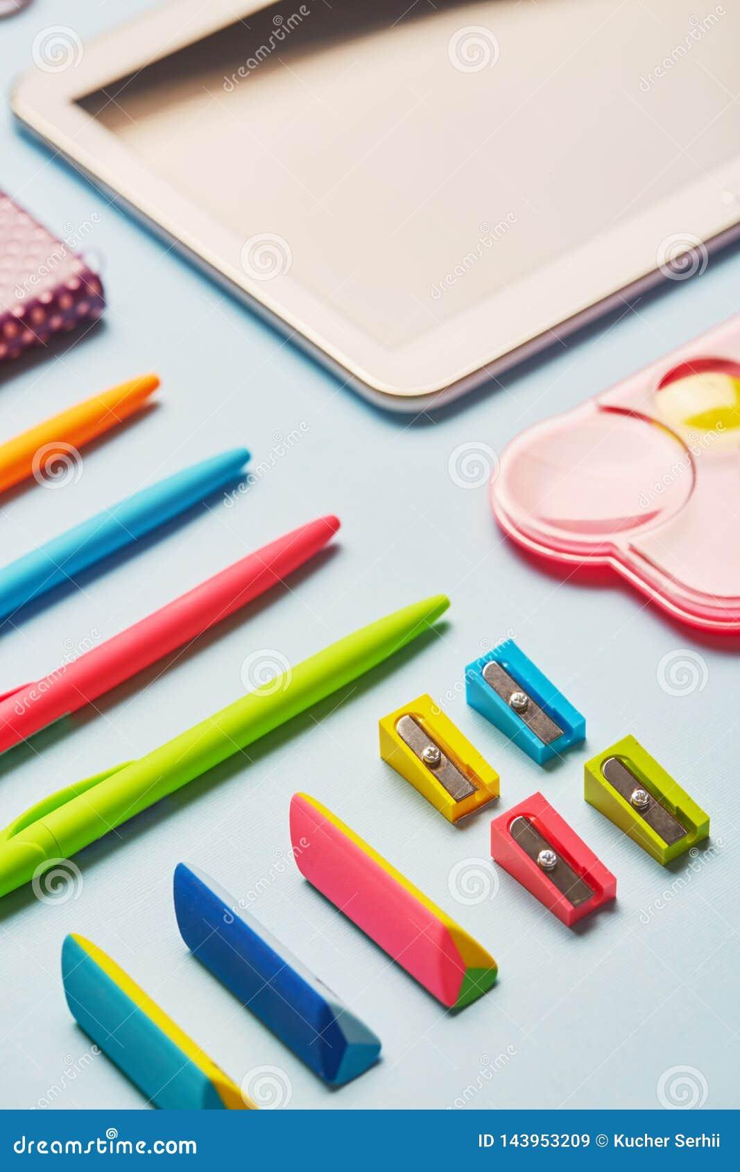 Ljusa gummi, vässare och pennor på en blå tabell