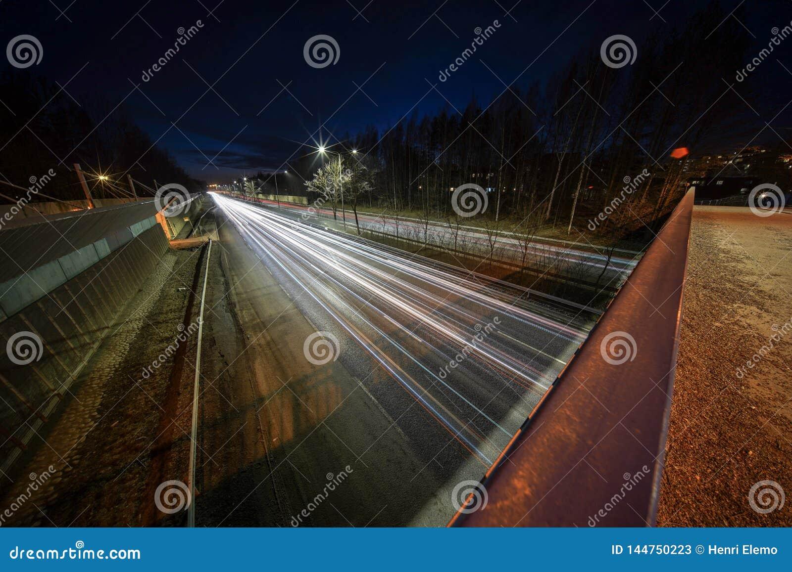 Ljusa slingor från bilar på Kehä 1 på Helsingfors fångade på natten med den mycket breda vinkellinsen och lång exponerin