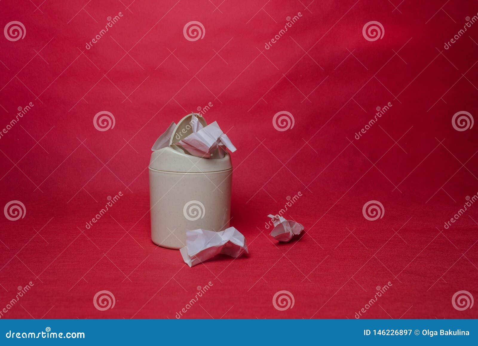 Ljust avfallfack på röd bakgrund Closeup av skrynkliga ark av papper Begrepp av miljö- återanvändande pappers- avfalls