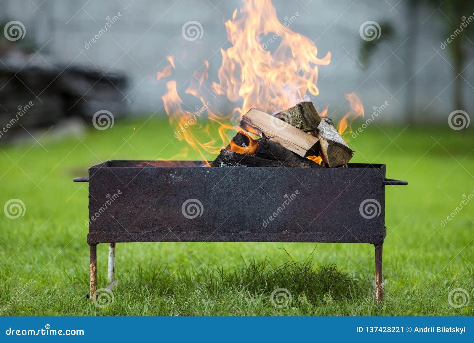 Ljust bränna i metallaskvedträt för grillfest utomhus- Campa, säkerhets- och turismbegrepp