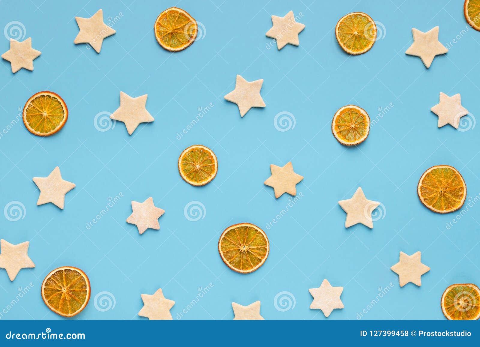 Ljust rödbrun kakor för jul och torkade apelsiner på blå bakgrund