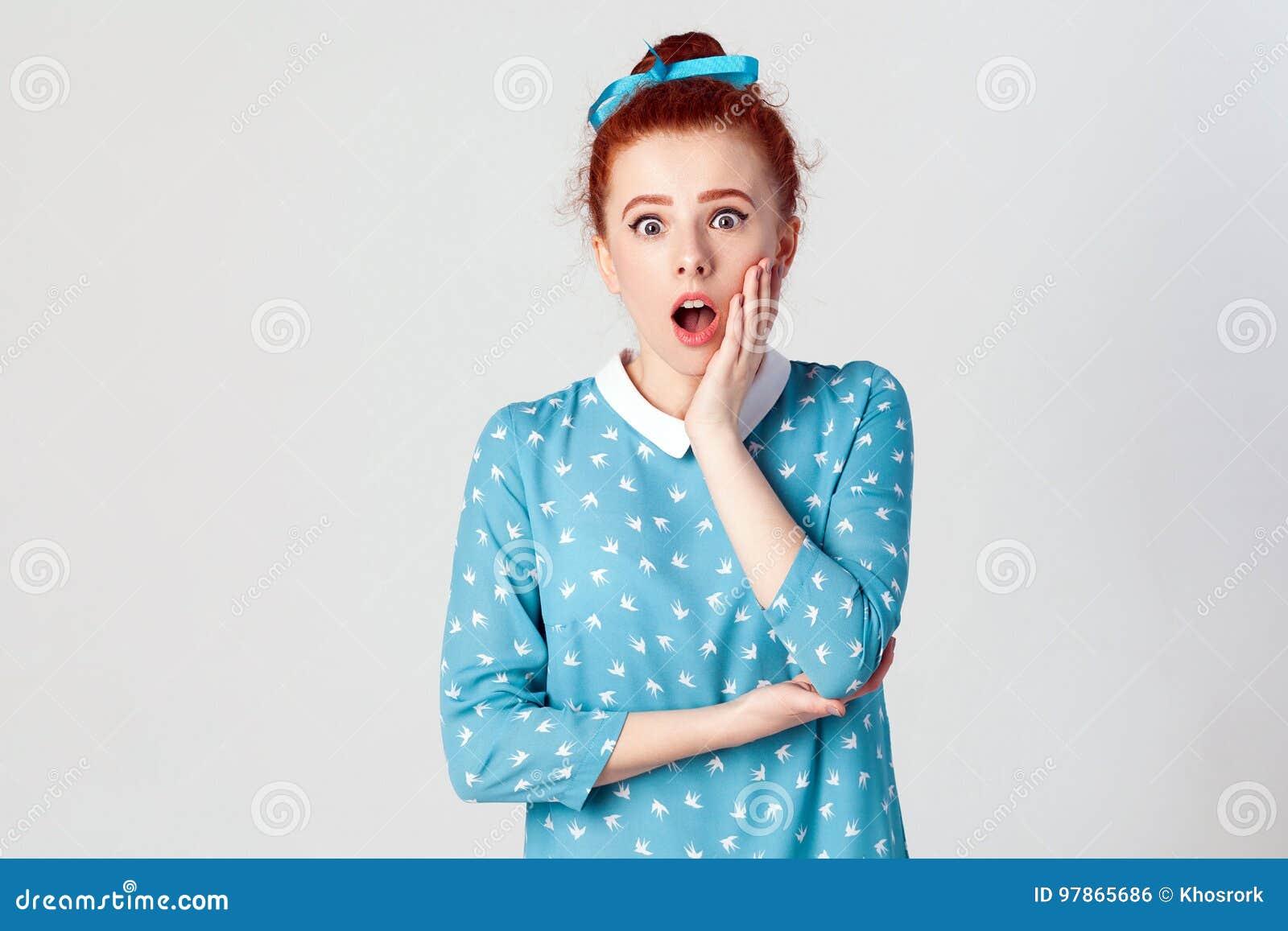 Ljust rödbrun ung flicka som skriker med chock som rymmer händer på hennes kinder Isolerat studioskott på grå bakgrund