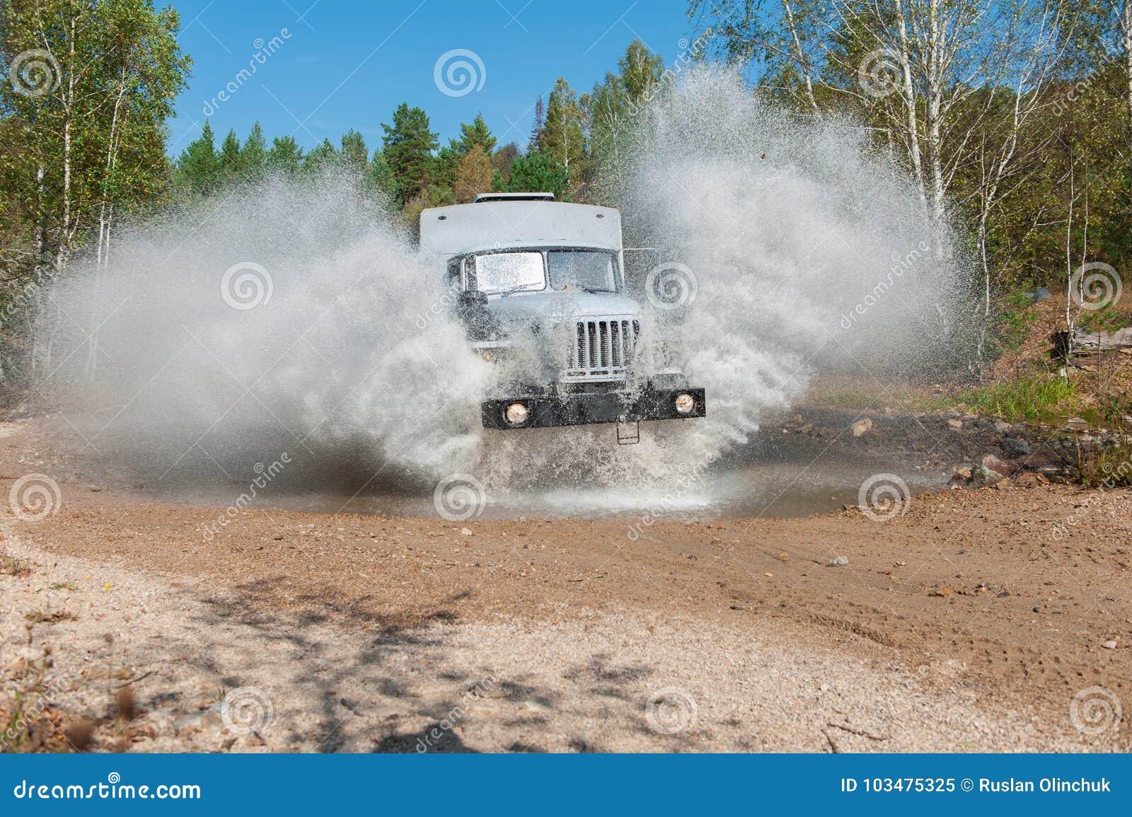 LKW-Durchläufe durch eine Pfütze
