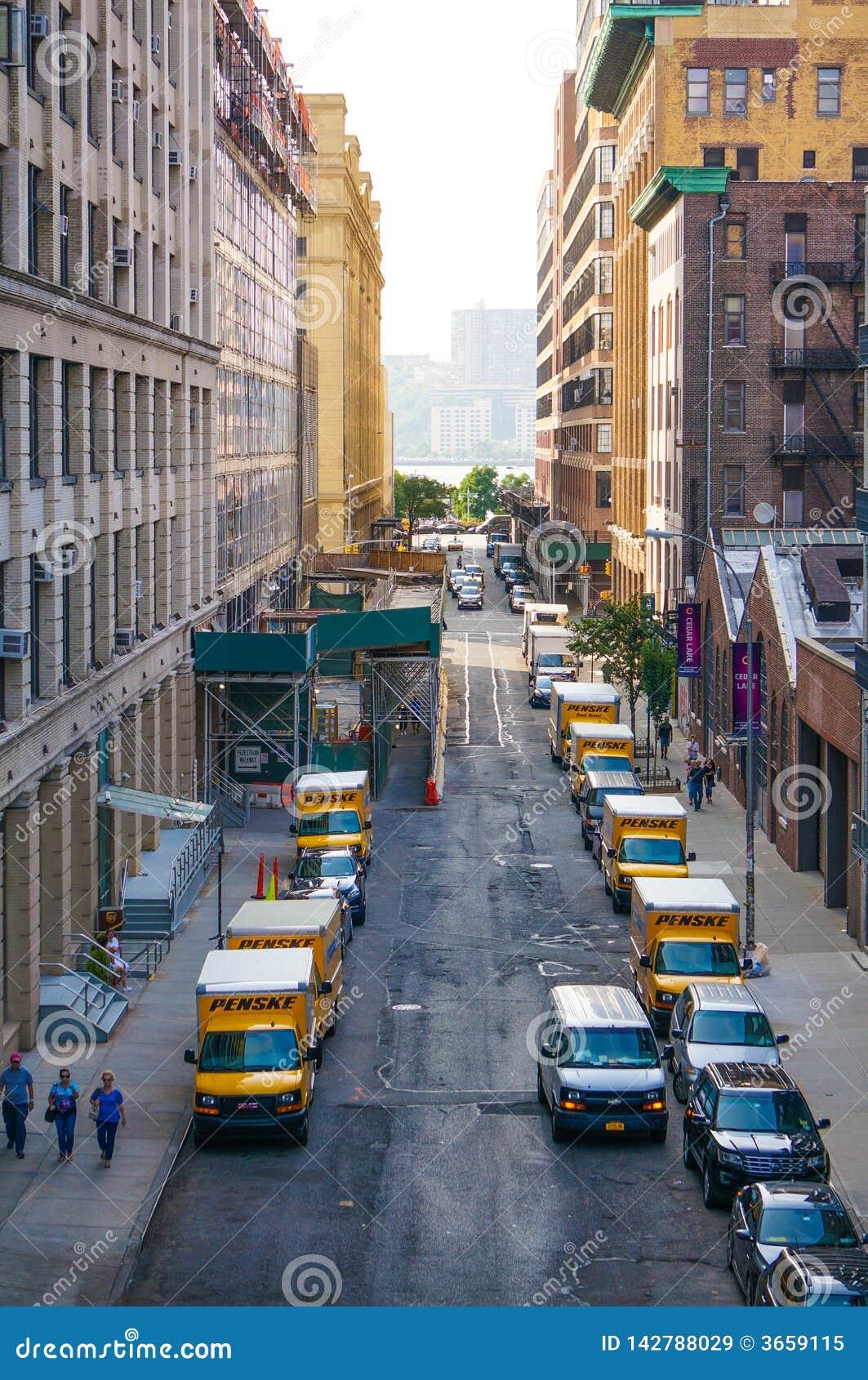 LKWs 'Penske 'in Folge in der schmalen Straße von NYC mit den Leuten, die vorbei gehen