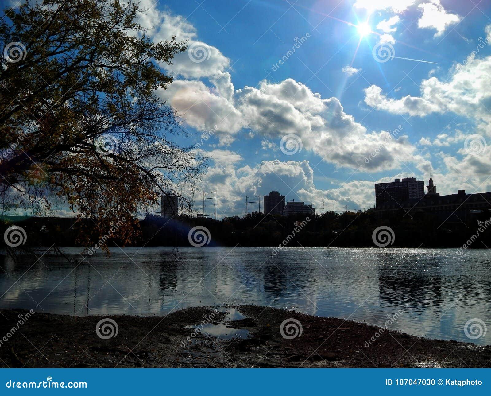 Llamarada brillante de Sun sobre un horizonte del edificio de New Jersey por el Riverbank de Raritan