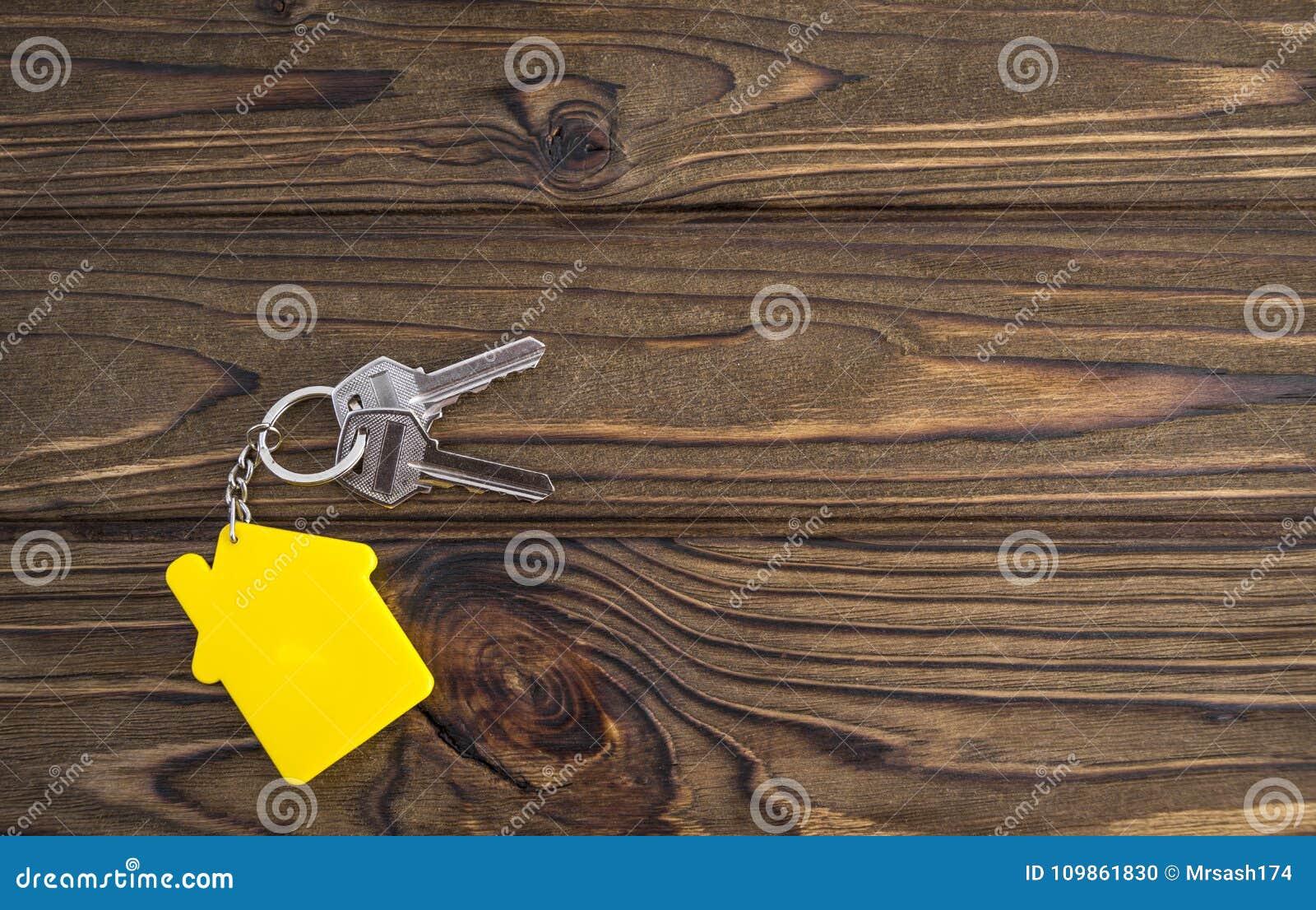 Llave con llavero formado amarillo de la casa en cadena en el fondo de madera de la textura