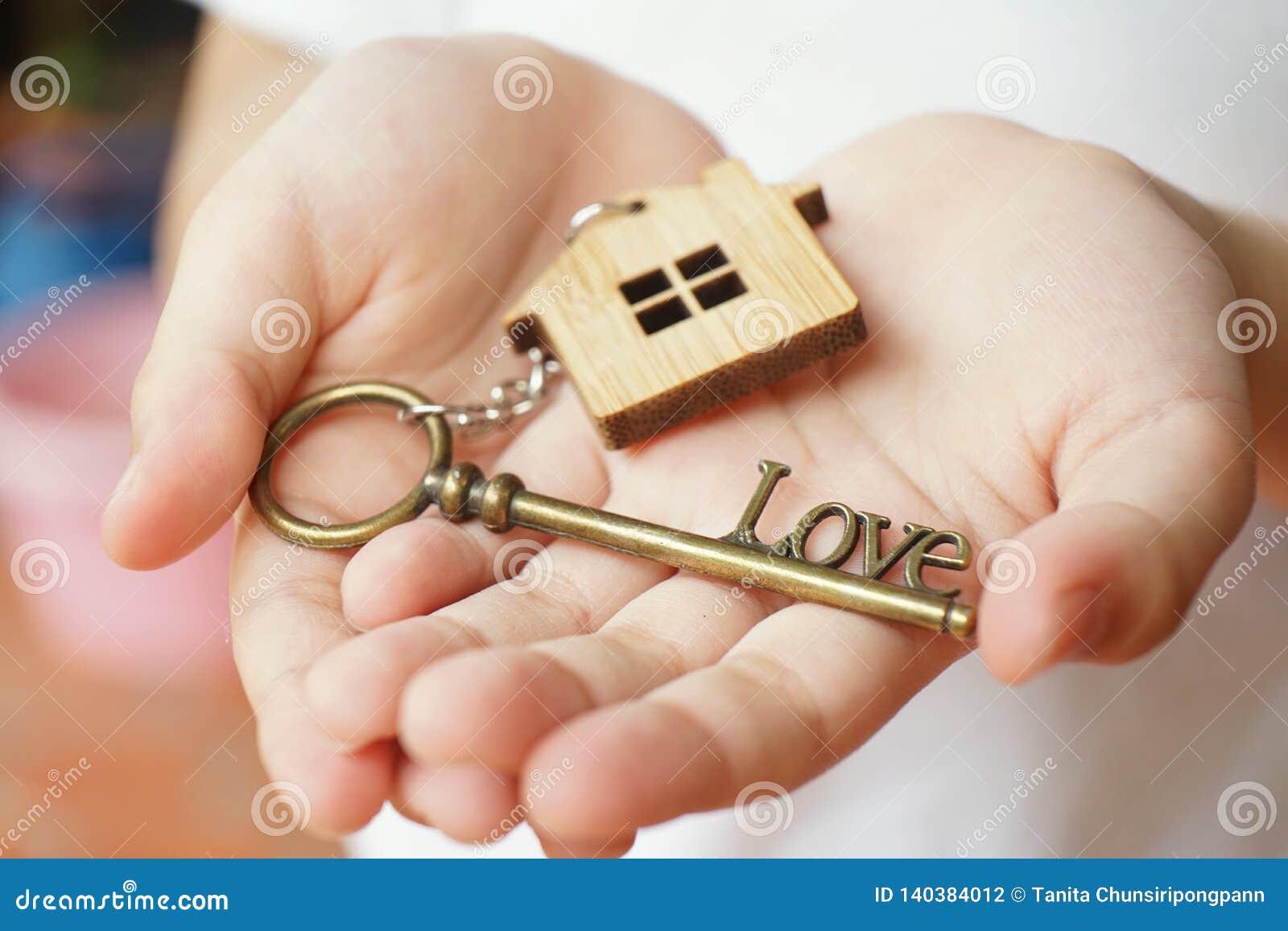 Llavero casero de madera con llave antigua de la forma del amor en el woman& x27; mano de s Un regalo al amante y a la familia Co