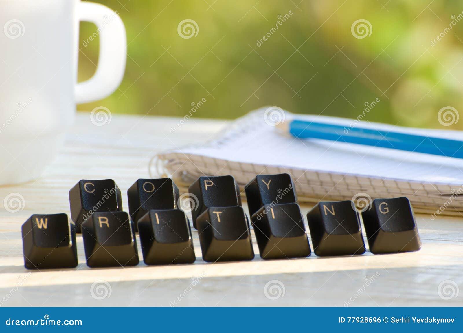 Llaves de ordenador en una tabla blanca, la palabra Copywriting, el cuaderno y la taza en fondo verde