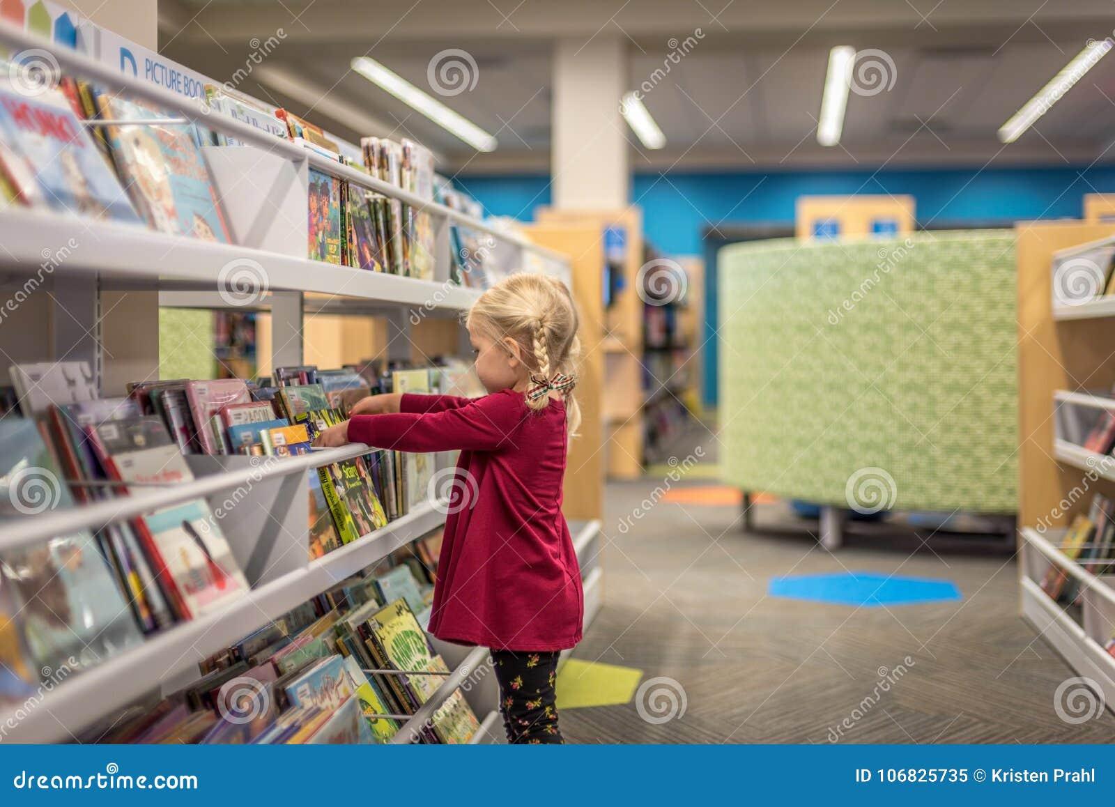 Llittle dziewczyna wybiera książki przy biblioteką