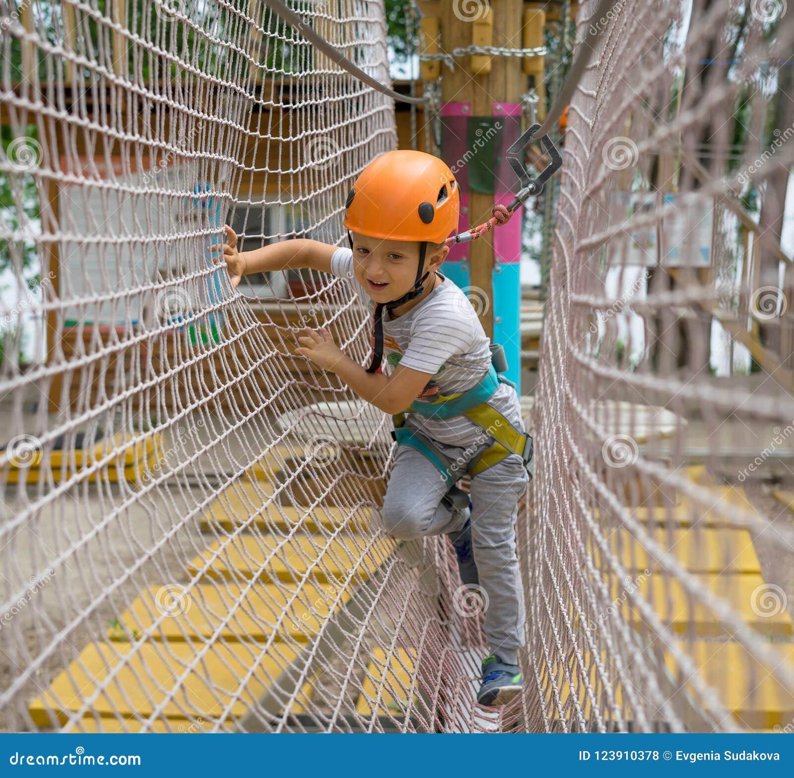Lo scalatore felice e sorridente un piccolo lega un nodo su una corda Una persona sta preparando per l ascesa Il bambino impara l
