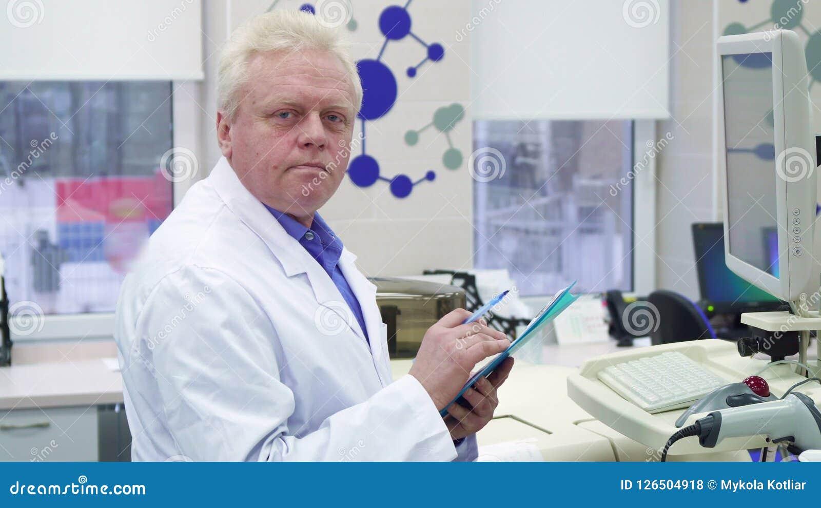 Lo scienziato maschio nota le informazioni sulla lavagna per appunti al laboratorio