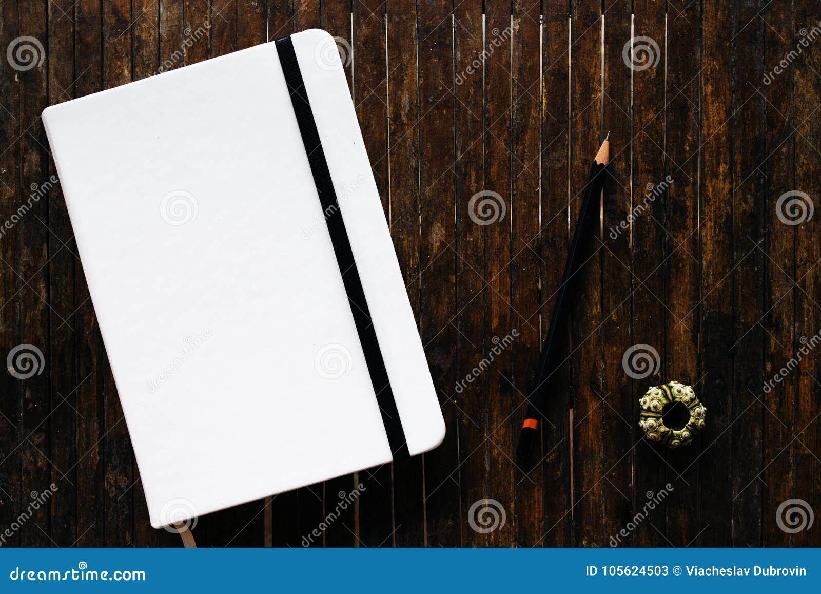Copertura In Legno Bianco : Lo sketchbook bianco della copertura con la matita nera sul piano