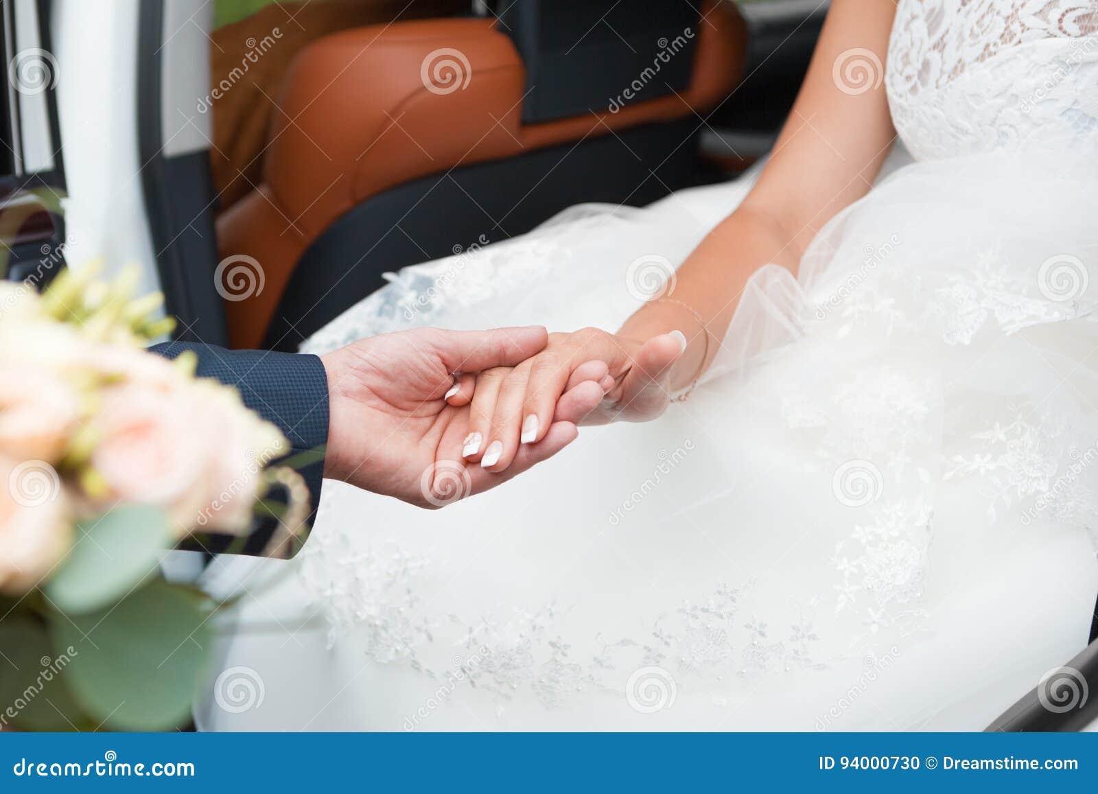Lo sposo aiuta la sposa ad uscire dell automobile