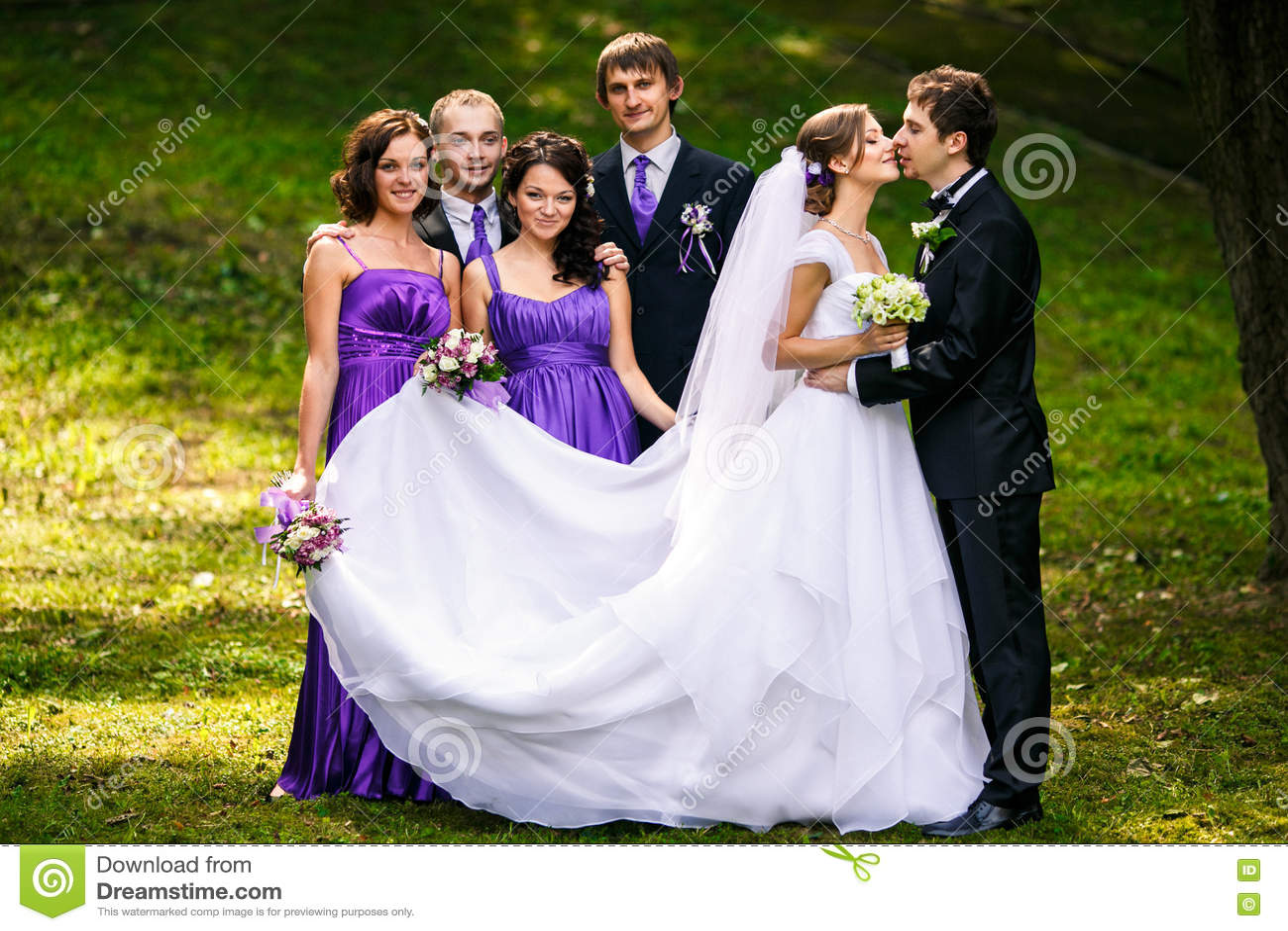 Lo sposo bacia una sposa mentre i suoi amici fa smorfie dietro lui