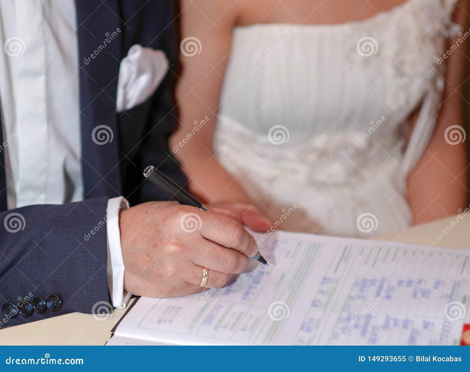 Lo sposo mette la sua firma nel documento del matrimonio, fuoco selettivo