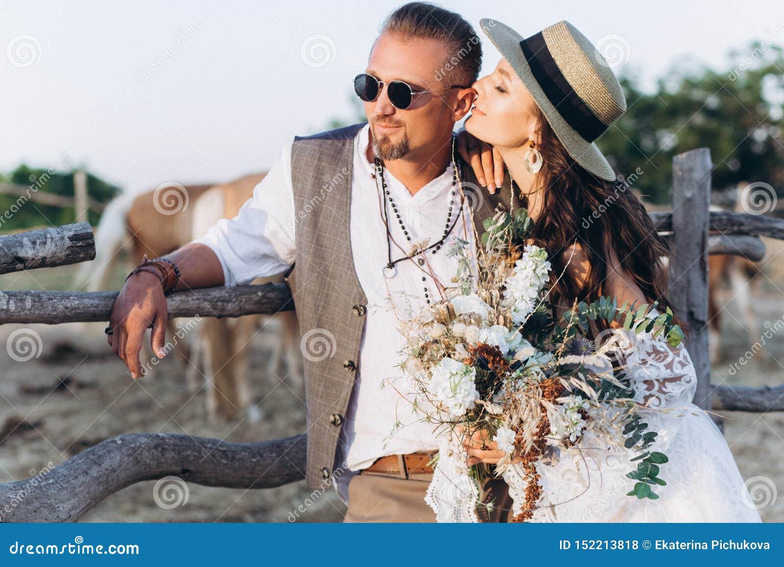 Lo sposo si è vestito nello stile del boho delicatamente bacia la sposa
