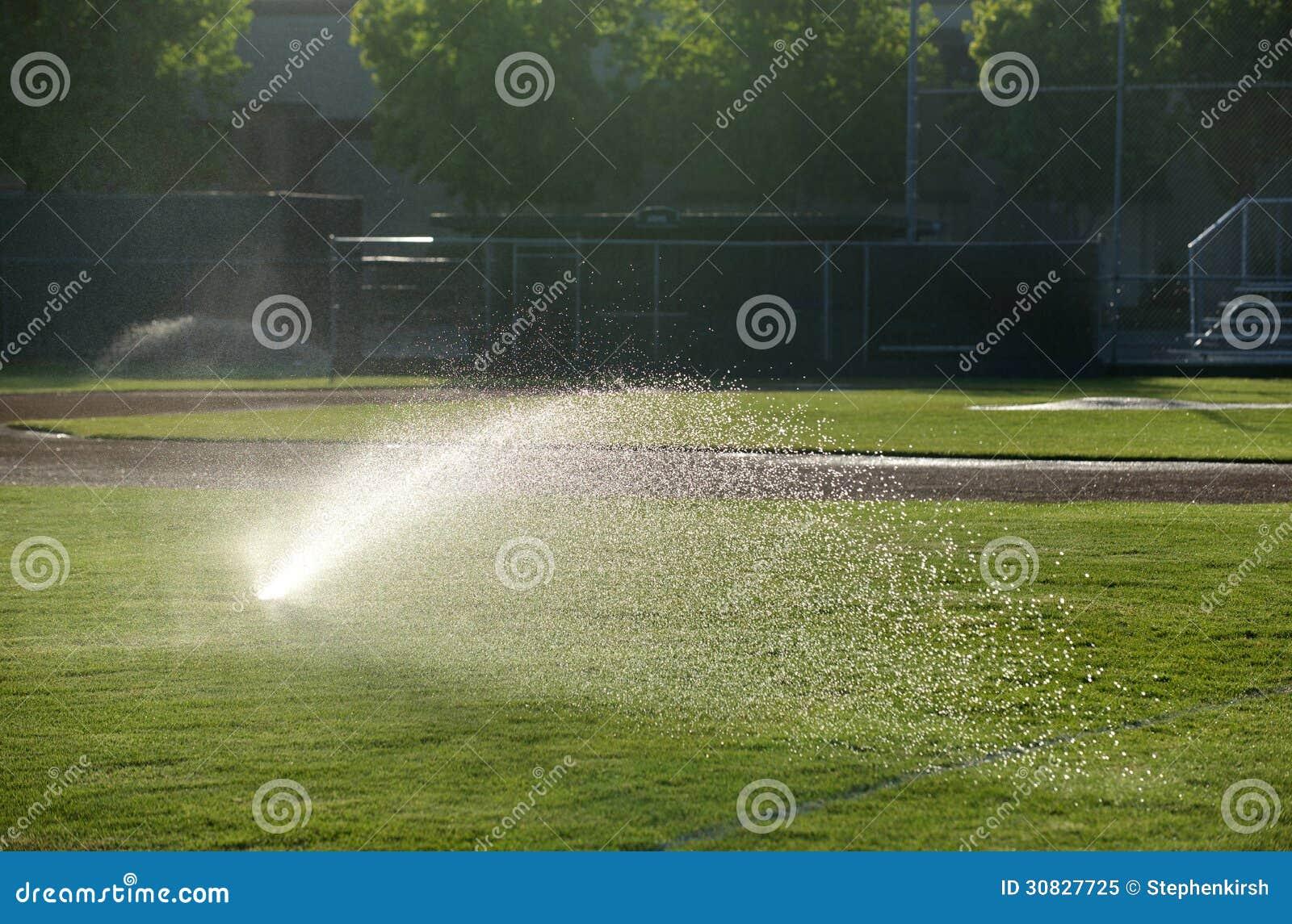 Lo spruzzatore del campo di baseball innaffia l erba, destra aguzza un giorno soleggiato