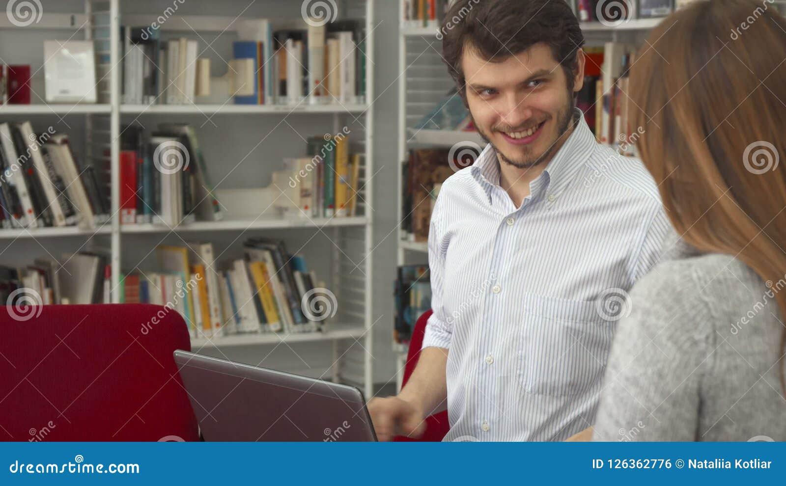 Lo studente maschio mostra al suo compagno di classe femminile qualcosa sul computer portatile alla biblioteca