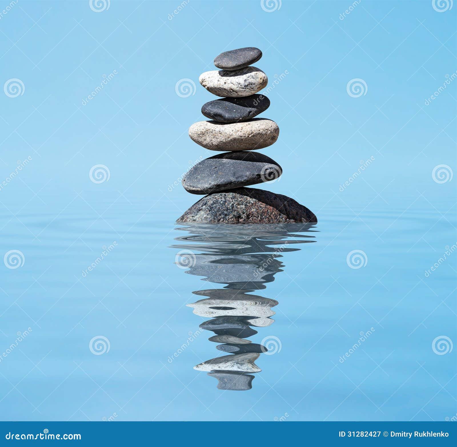 Lo zen ha equilibrato la pila delle pietre nel concetto di silenzio di pace dell equilibrio del lago
