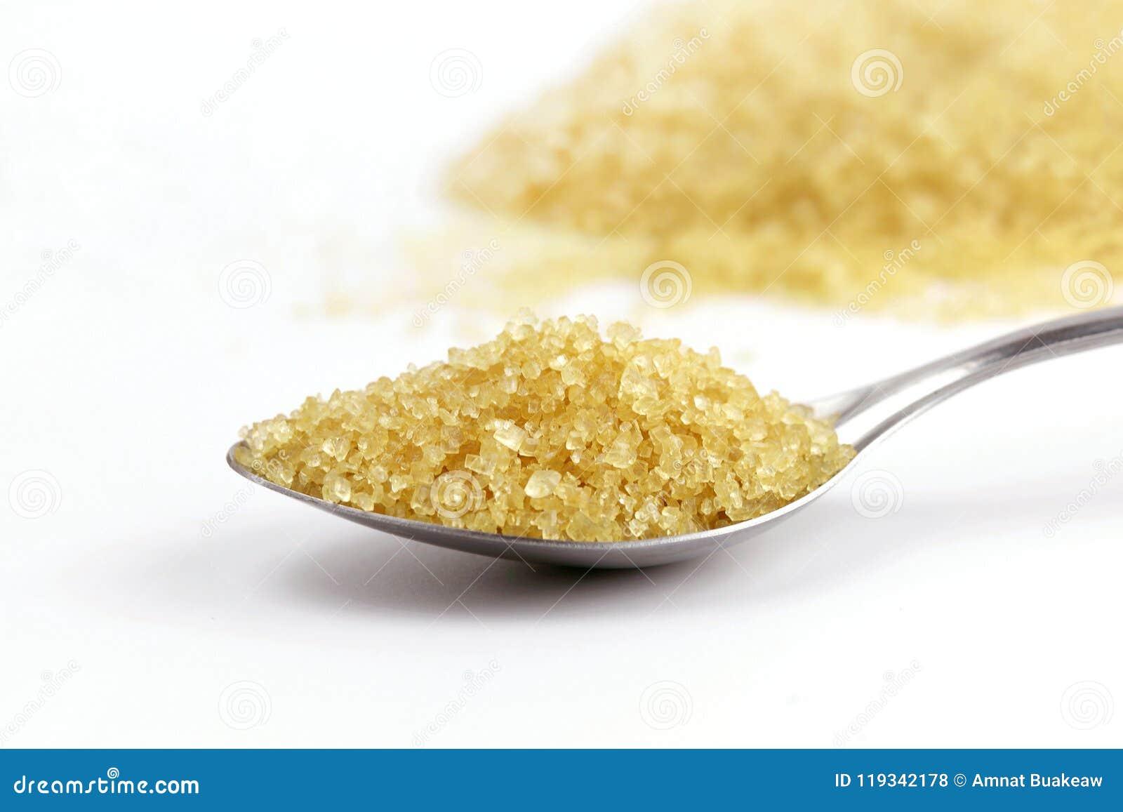 Lo zucchero in cucchiaio, zucchera il mucchio marrone dalla canna da zucchero su giallo dell acciaio inossidabile del cucchiaio e