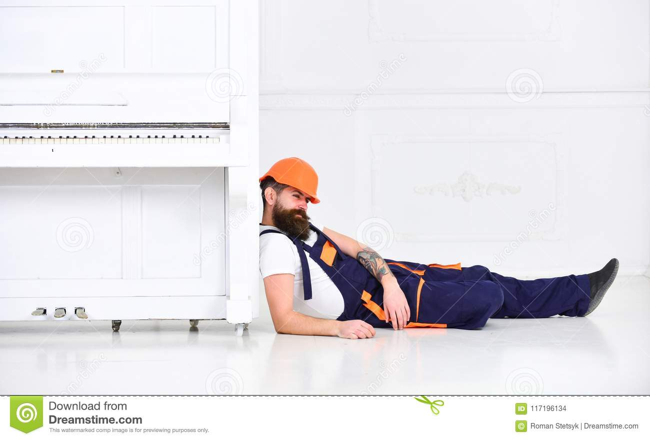Loader lean on piano instrument. Man with beard, worker in overalls and helmet fall asleep tired, white background