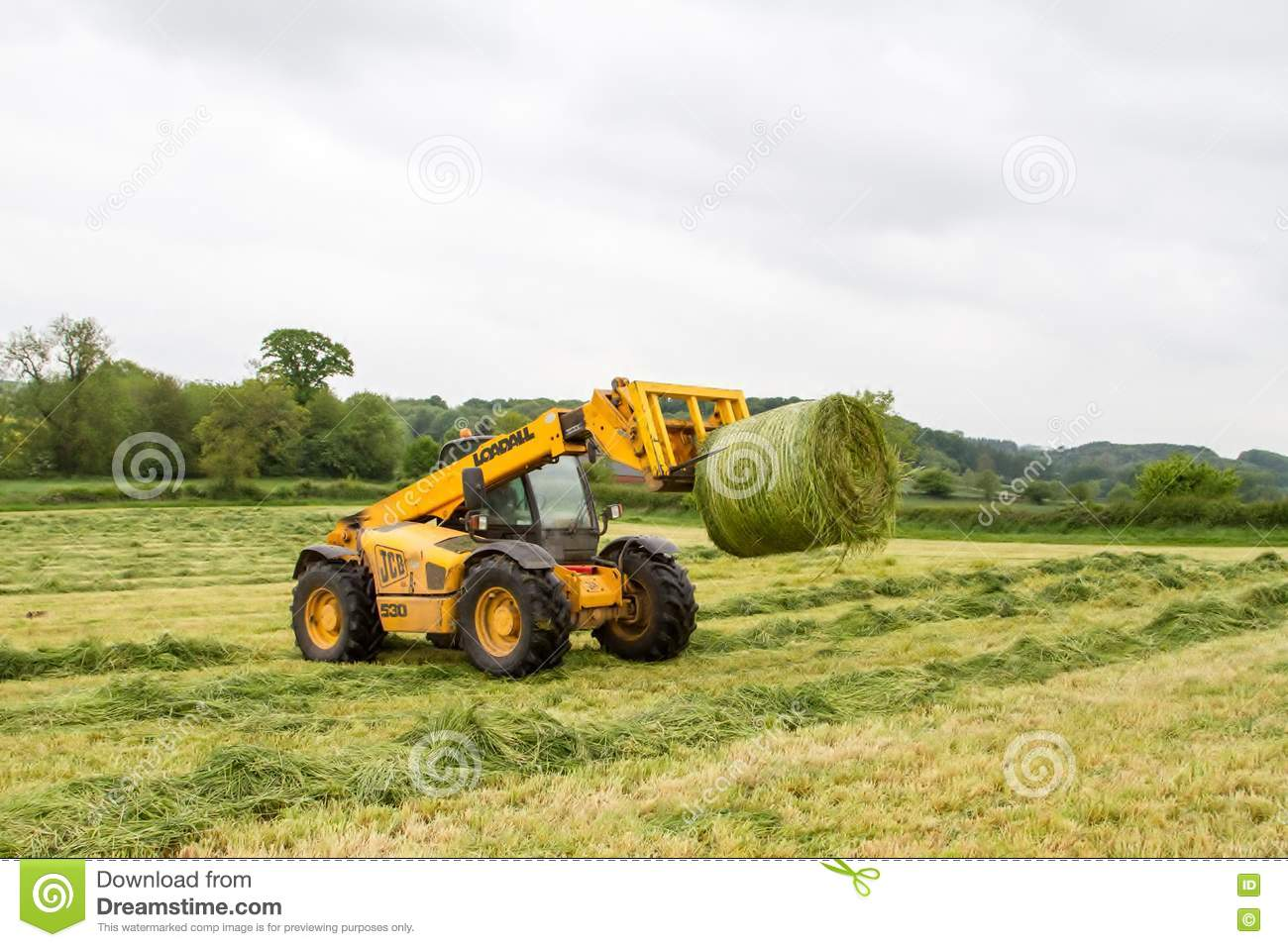Hay Tractor With Loader : Loader tractor moving a round bale from field editorial