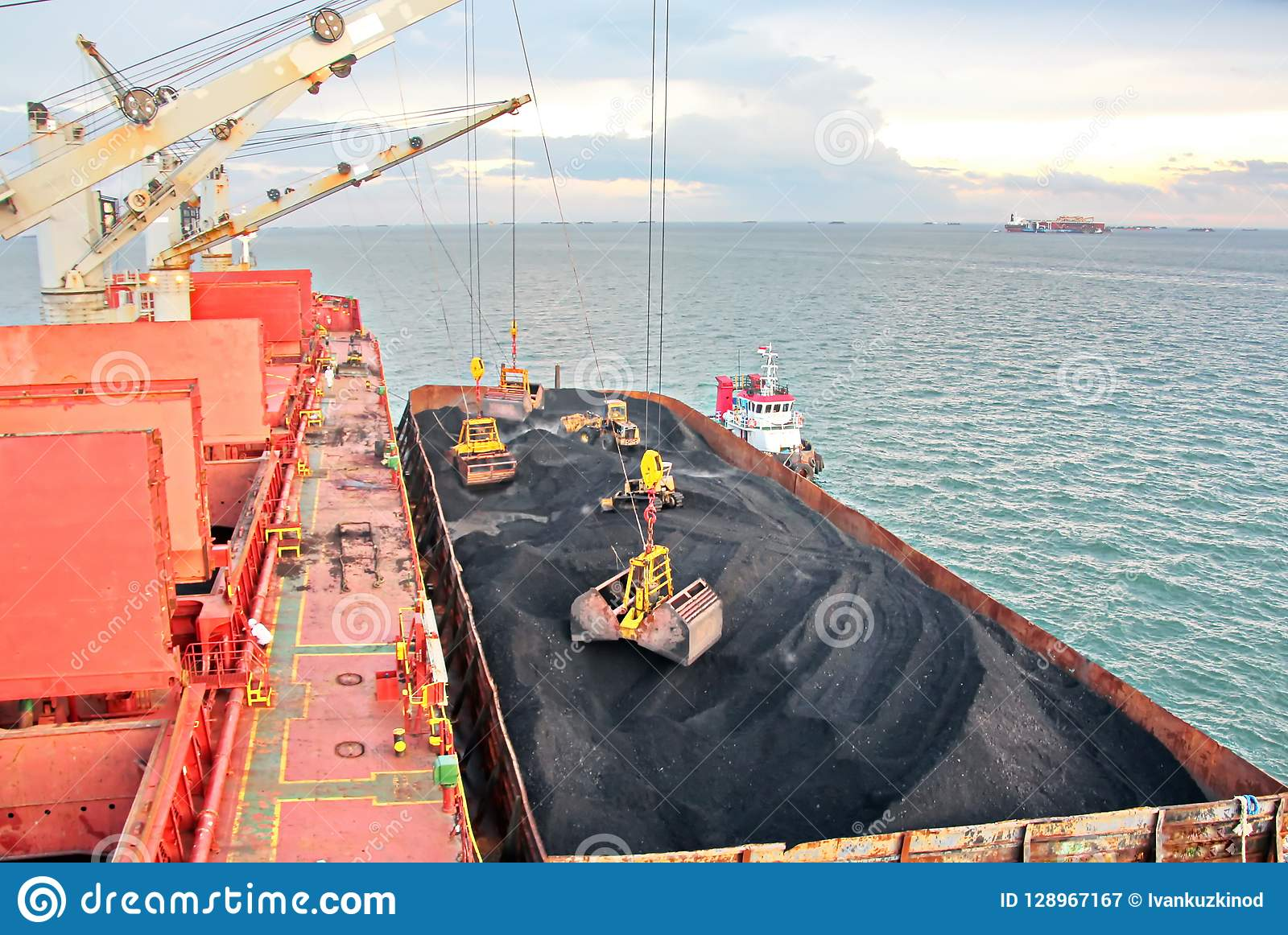 Loading coal from cargo barges onto a bulk carrier using ship cranes and grabs at the port of Samarinda, Indonesia.