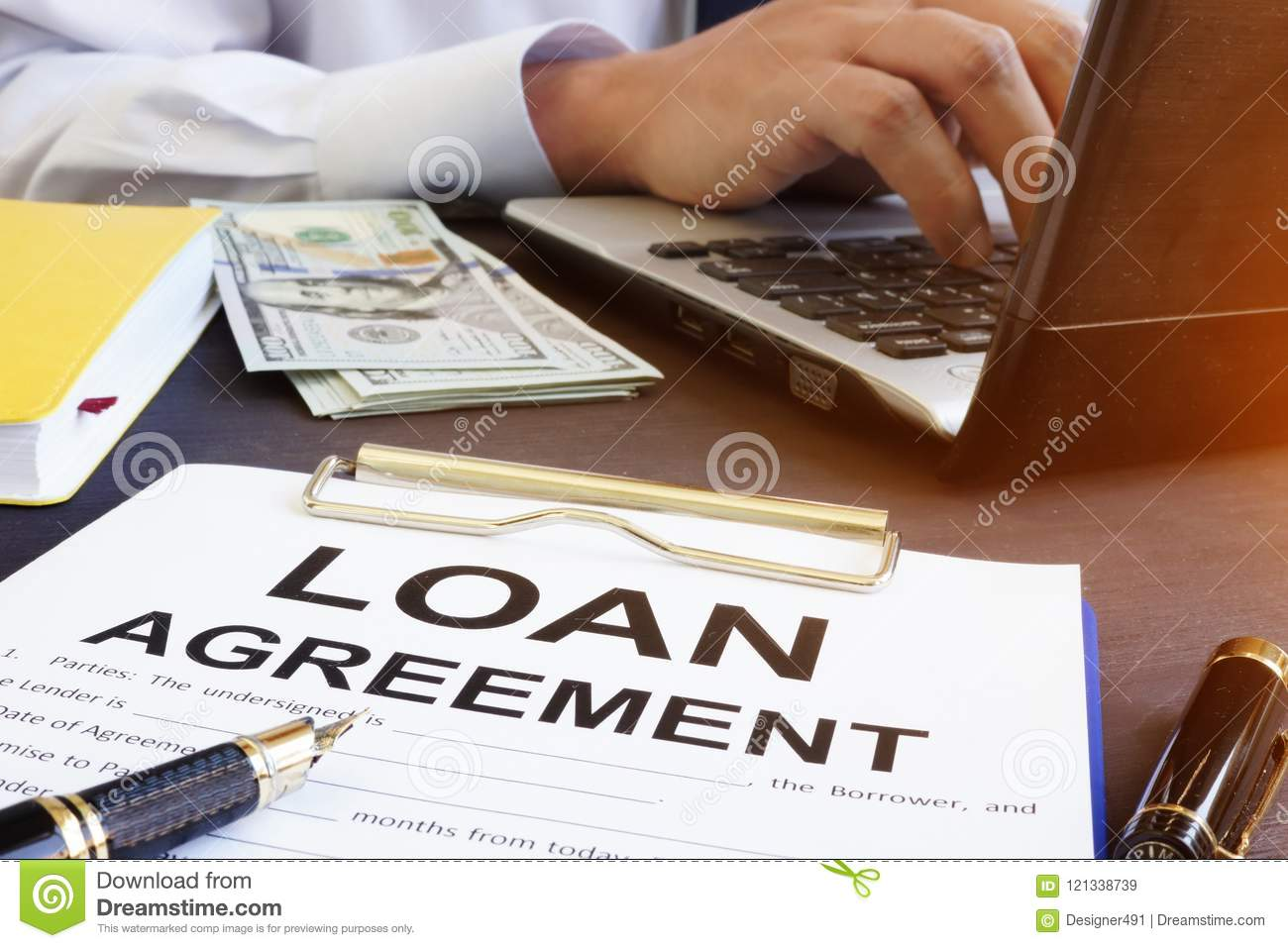 Loan agreement and money on a desk.