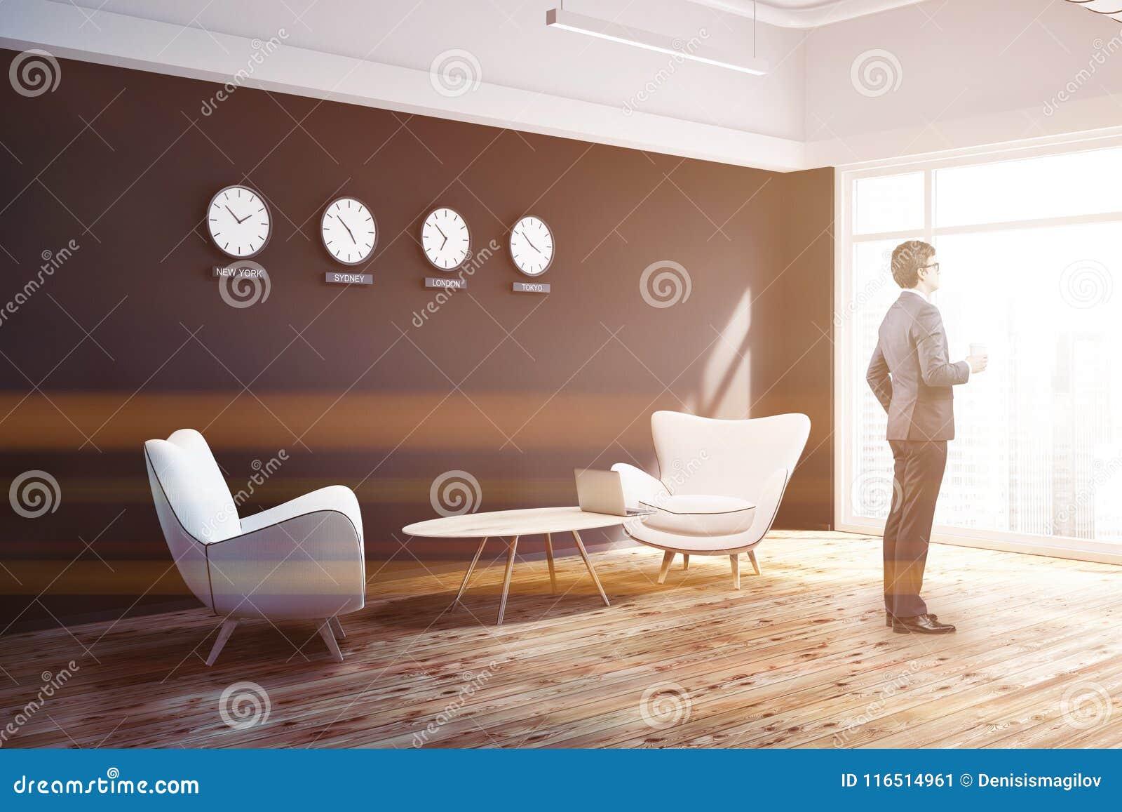 Lobby noir de bureau de mur avec des horloges vue de côté homme