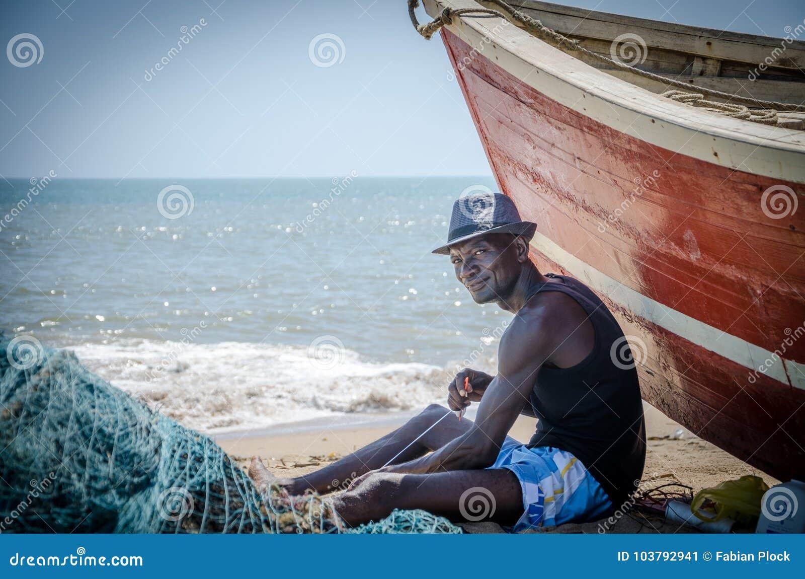 LOBITO, ANGOLA - 9 DE MAIO DE 2014: Pescador angolano não identificado que senta-se na frente do barco de pesca vermelho em redes