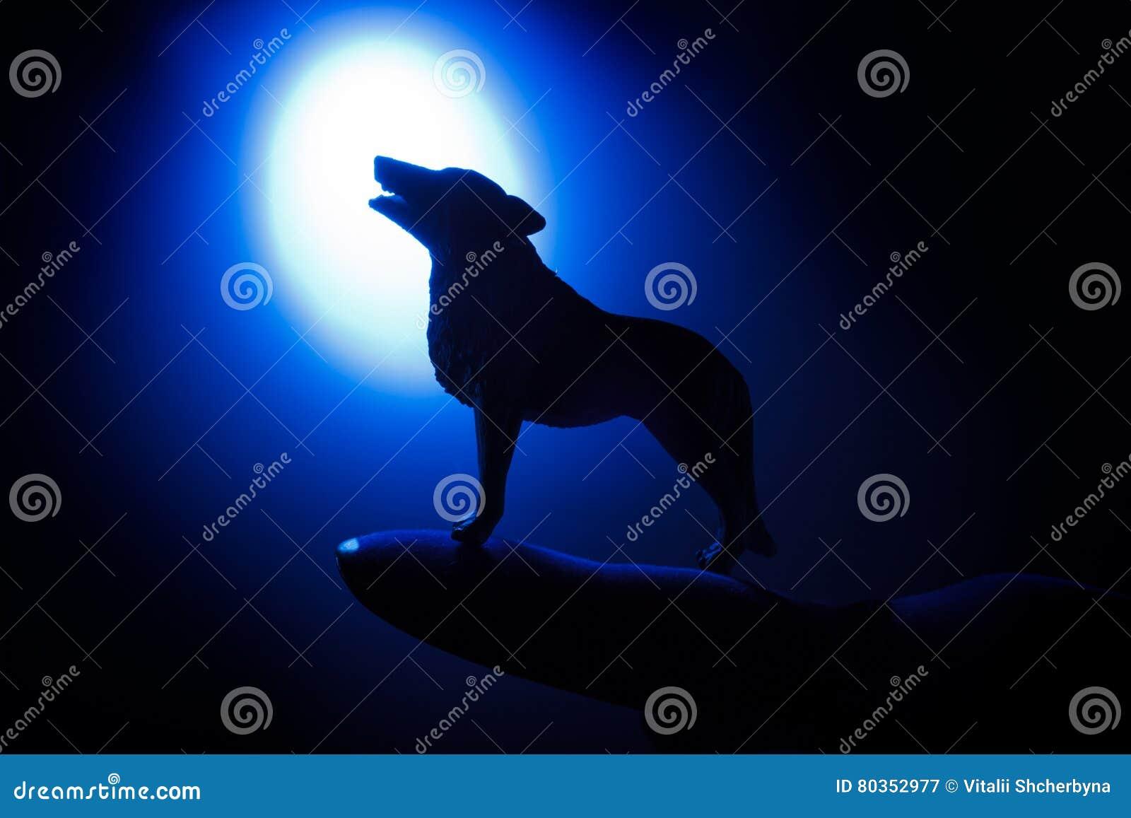 Lobo en silueta que grita a la Luna Llena
