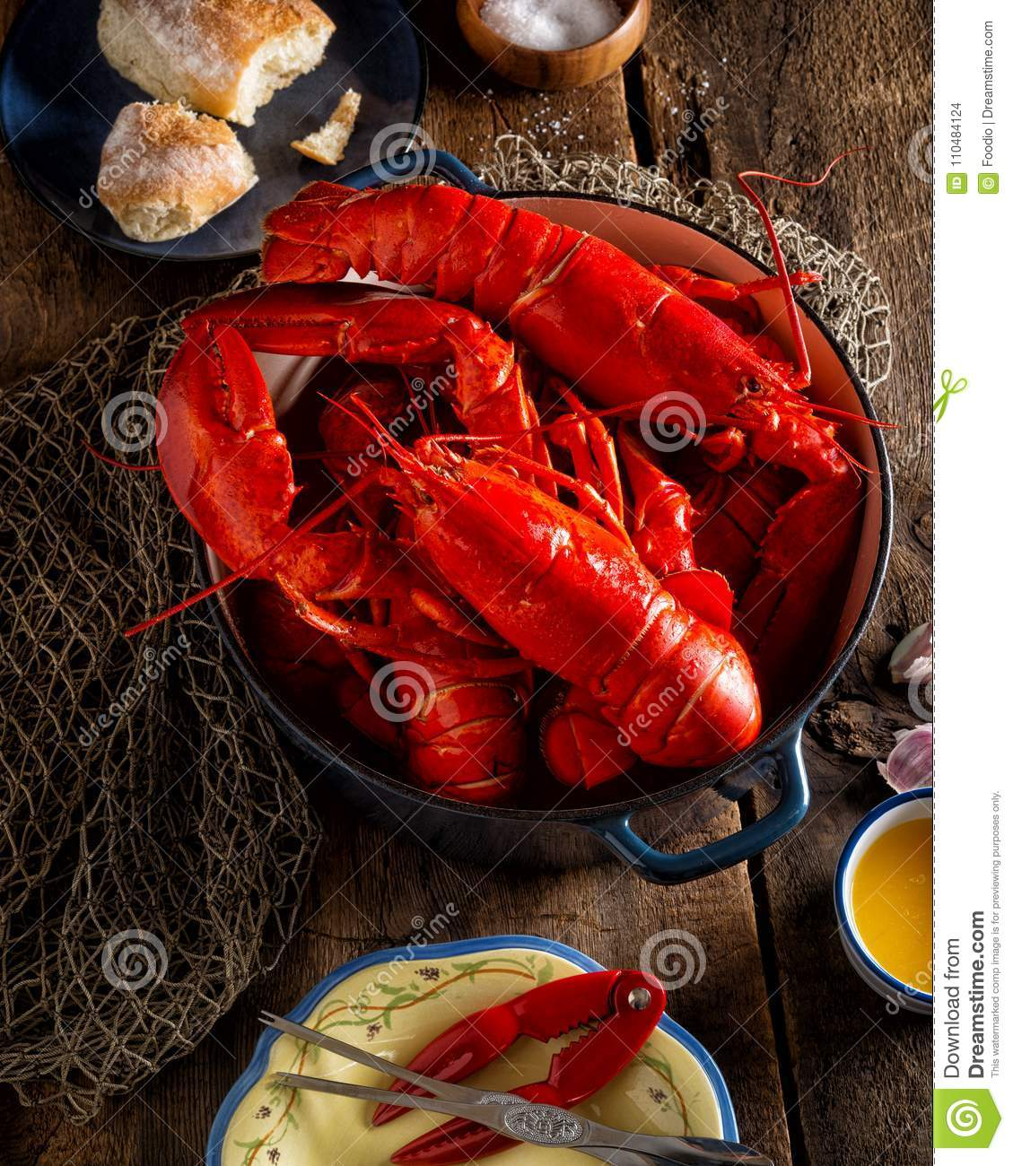 Lobsters in a pot on a rustic wooden table.