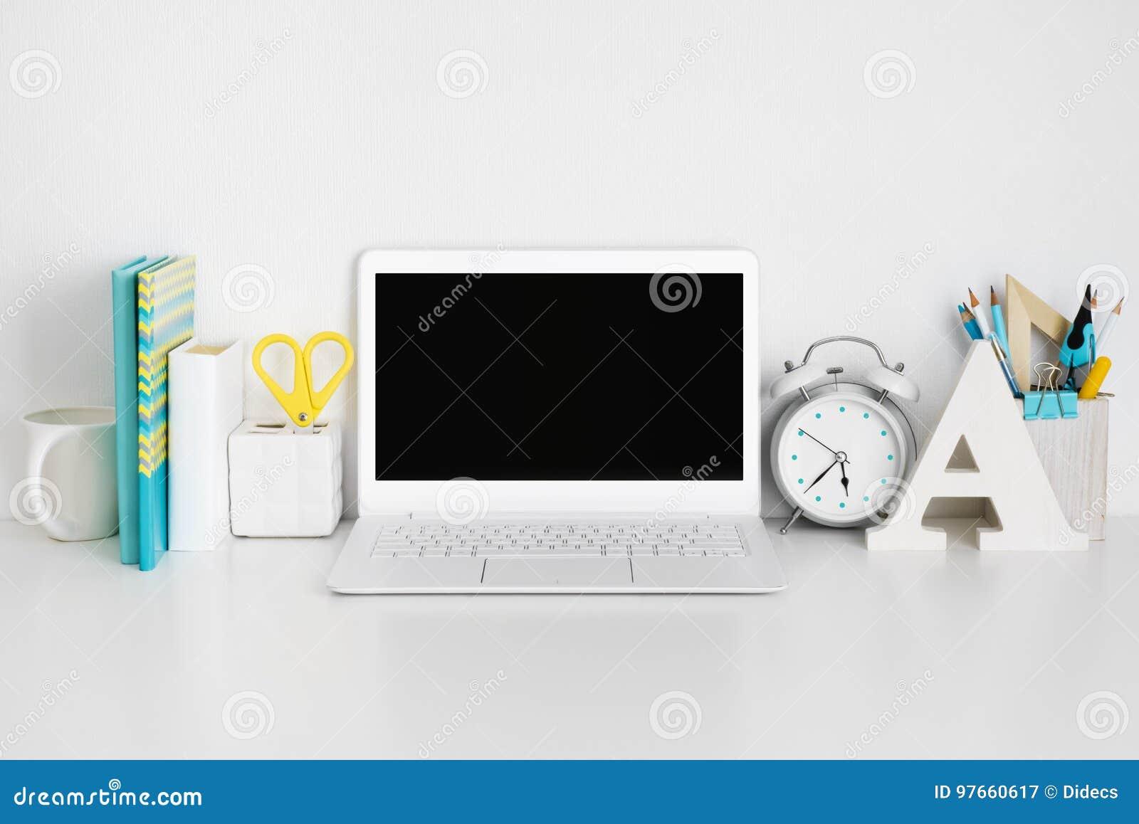 Local de trabalho com o portátil na tabela branca, conceito do negócio ou da educação