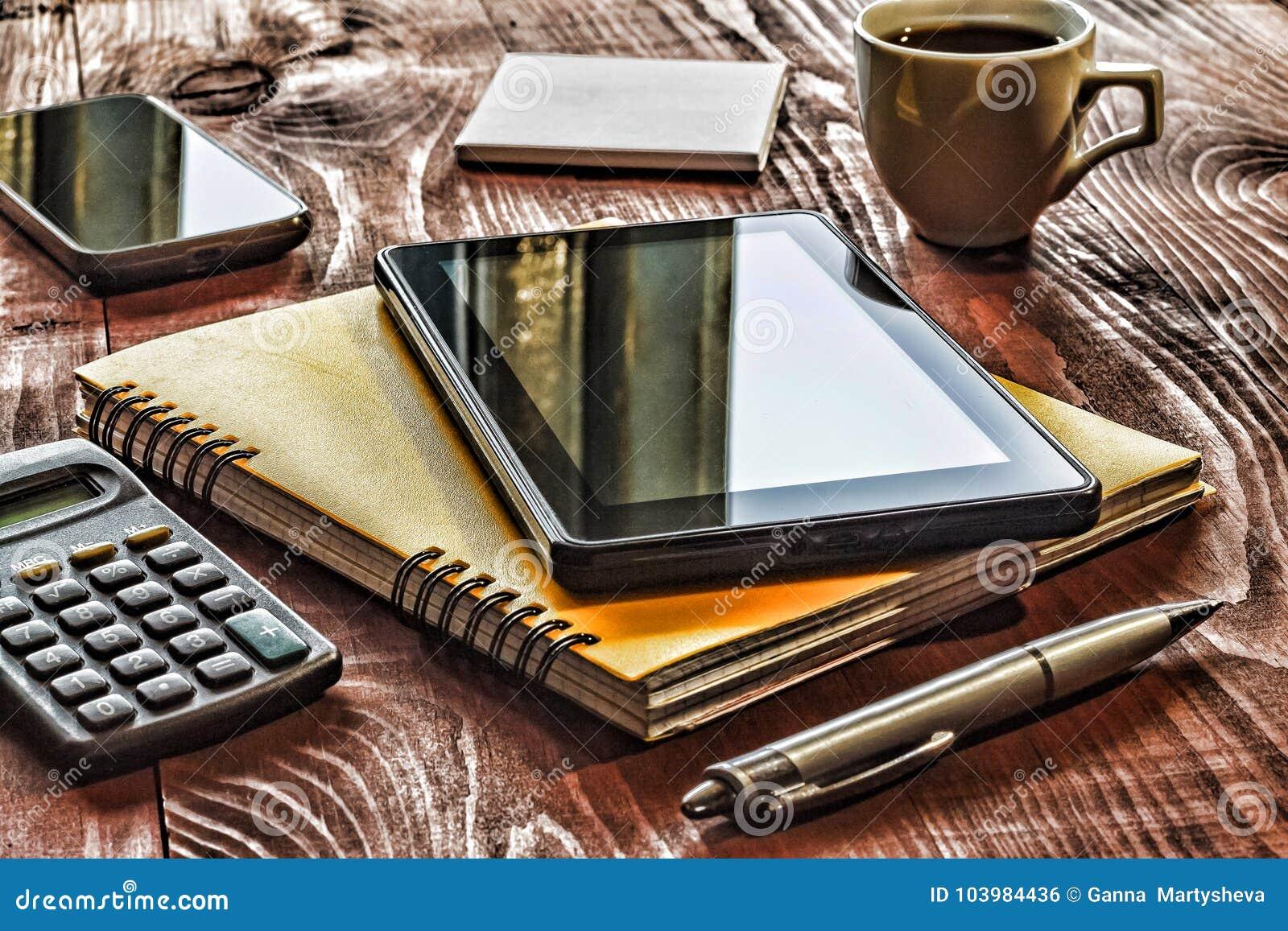 Local de trabalho da disposição do close up no escritório Tiro quadrado, PC da tabuleta, caderno, pena, etiquetas