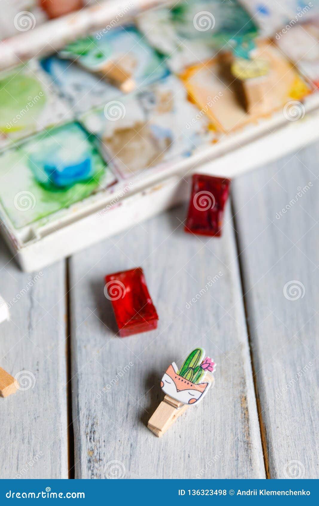 Local de trabalho do artista: Tabela branca de um artista com as ferramentas da arte para tirar