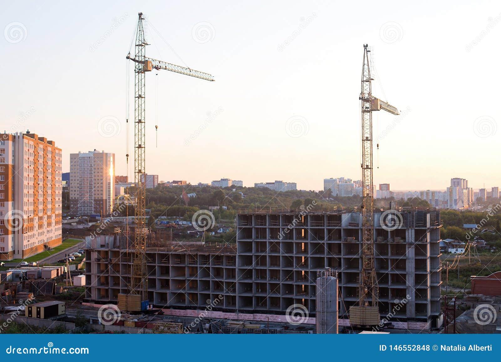 Local e guindastes de prédio de apartamentos na cidade no nascer do sol