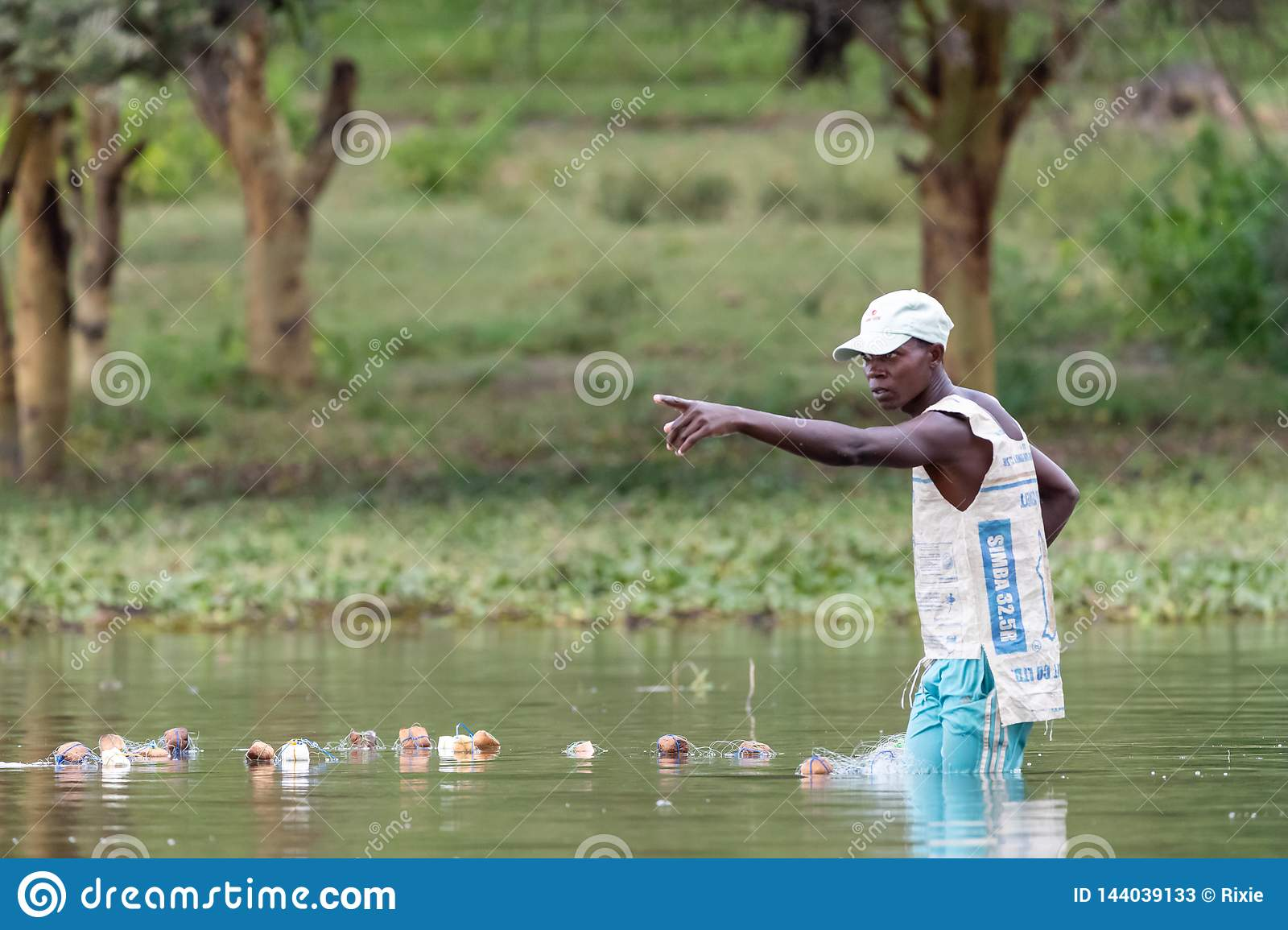 Local fisherman casts his nets in the shallow waters of Lake Naivasha