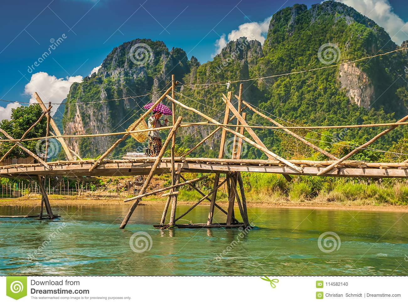 A local woman with a sun umbrella crosses a bamboo bridge in Laos